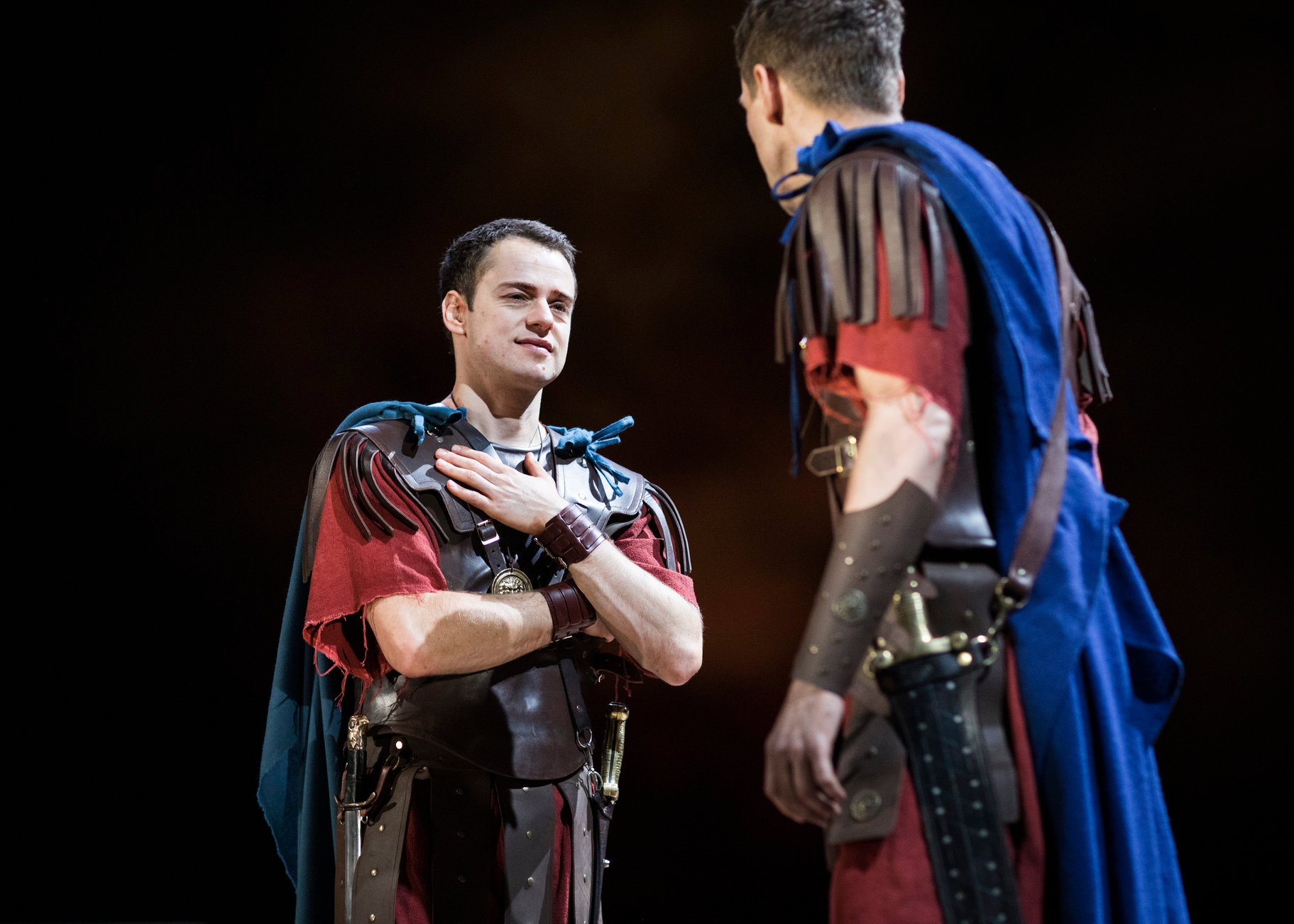 Cassius and Brutus prepare for war facing each other dressed in Roman uniform in the 2017 production of Julius Caesar.