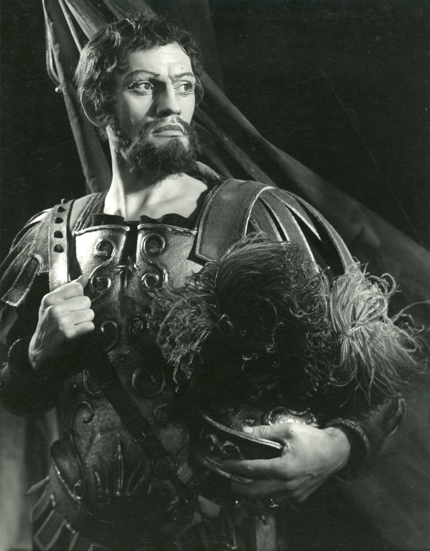 Brutus standing wearing armour and holding an elaborate helmet under his left arm