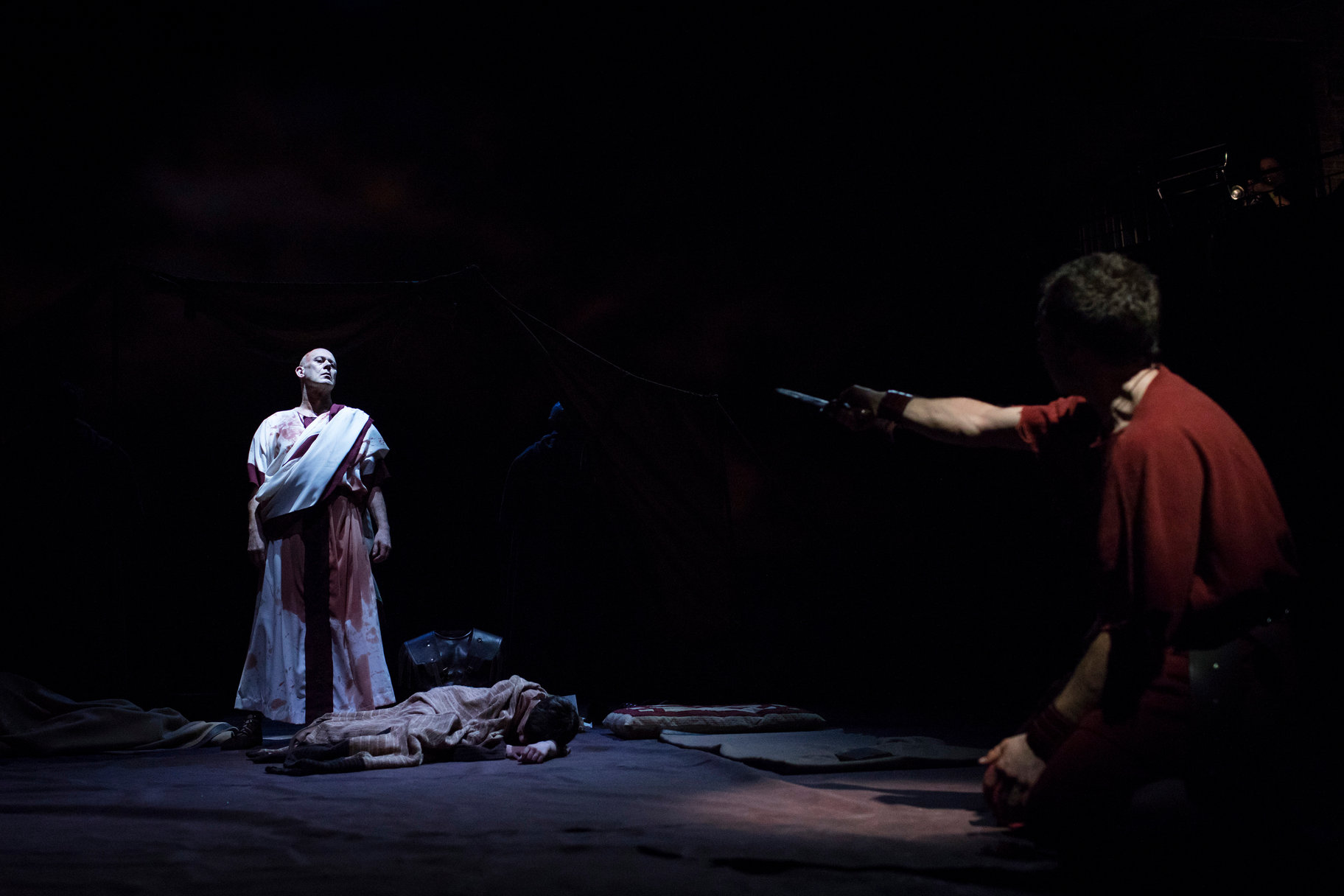Julius Caesar's ghost appears to Brutus. Brutus holds a knife out towards the ghost.