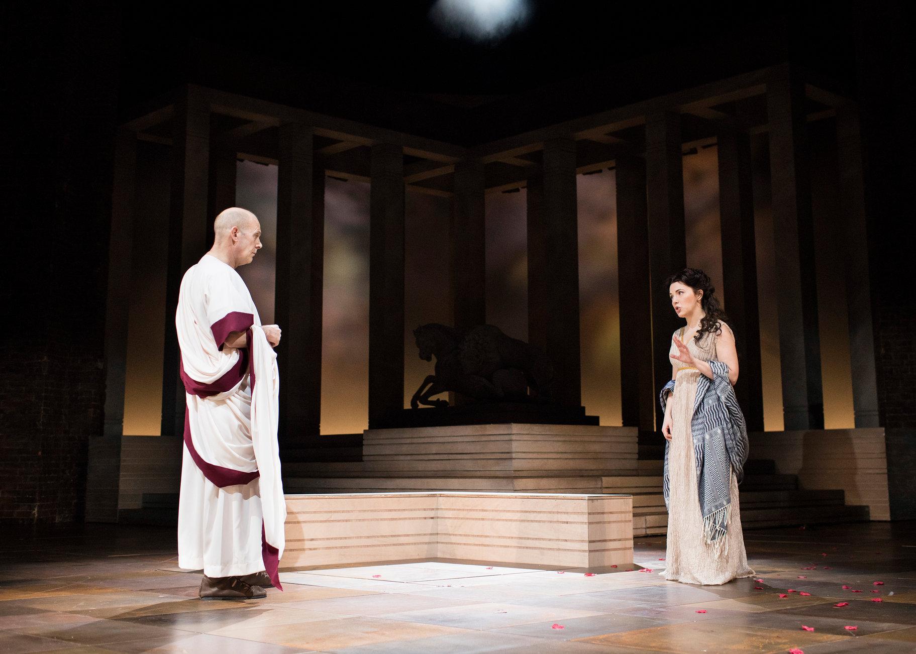 Calphurnia and Caesar stand far apart and talk in the 2017 production of Julius Caesar.