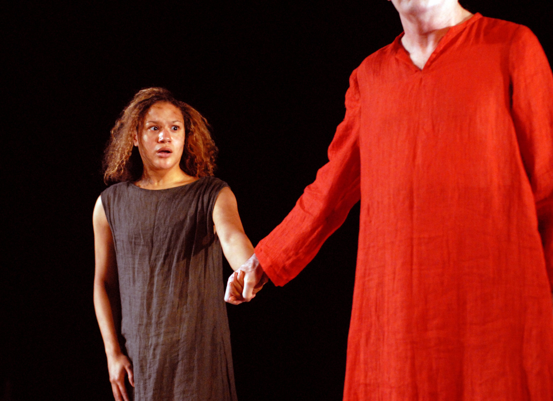 Calphurnia holding Caesar back by the hand as he walks away, wearing bright red in the 2006 production of Julius Caesar.