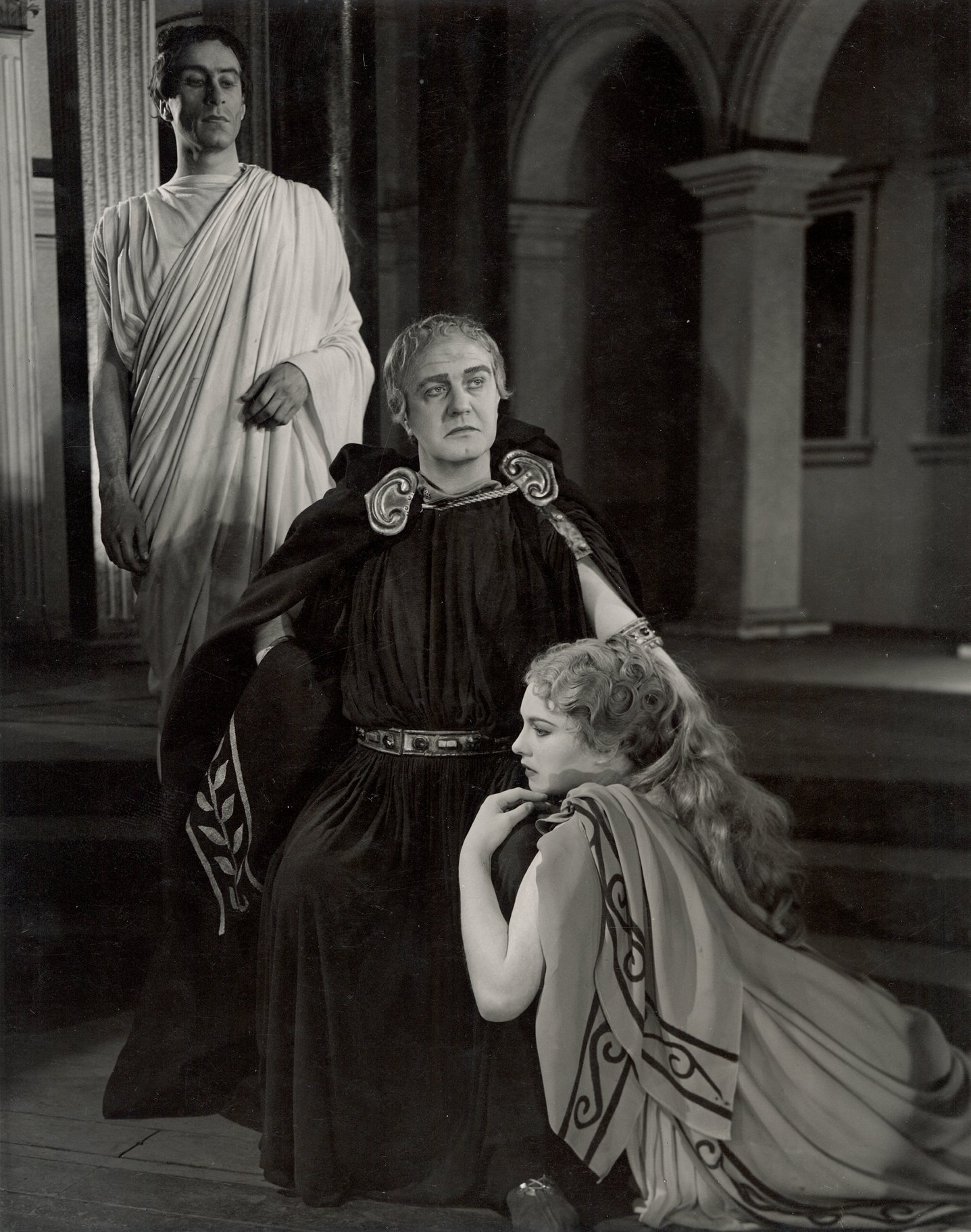Calphurnia draping herself over Caesar and clinging to his leg while he sits in state with Decius Brutus behind him in a toga in the 1950 production of Julius Caesar.
