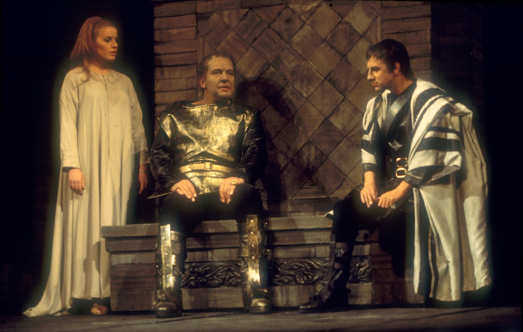 Calphurnia standing beside Caesar as he hears from Decius Brutus who is kneeling in the 1968 production of Julius Caesar.