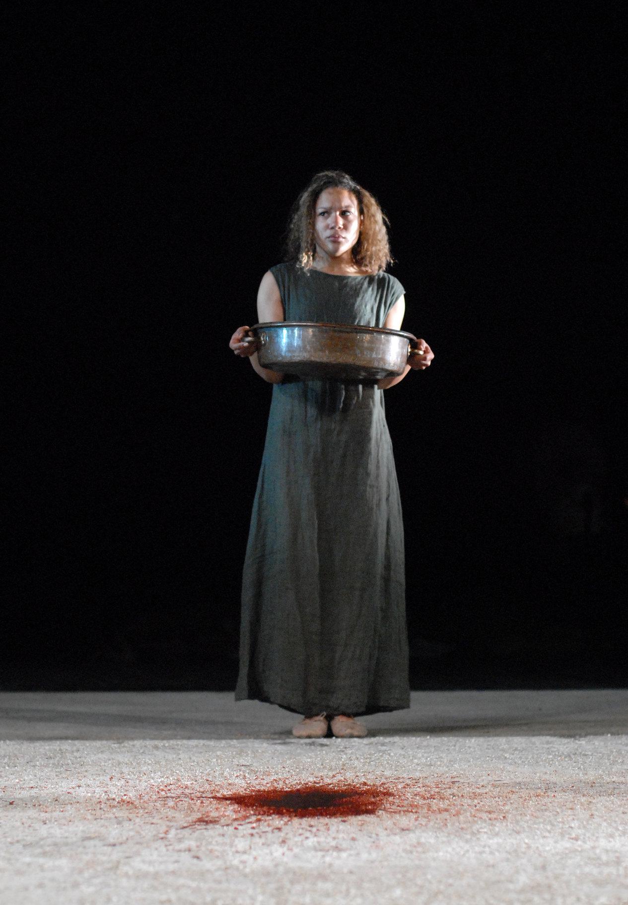 Calphurnia standing holding a metal dish