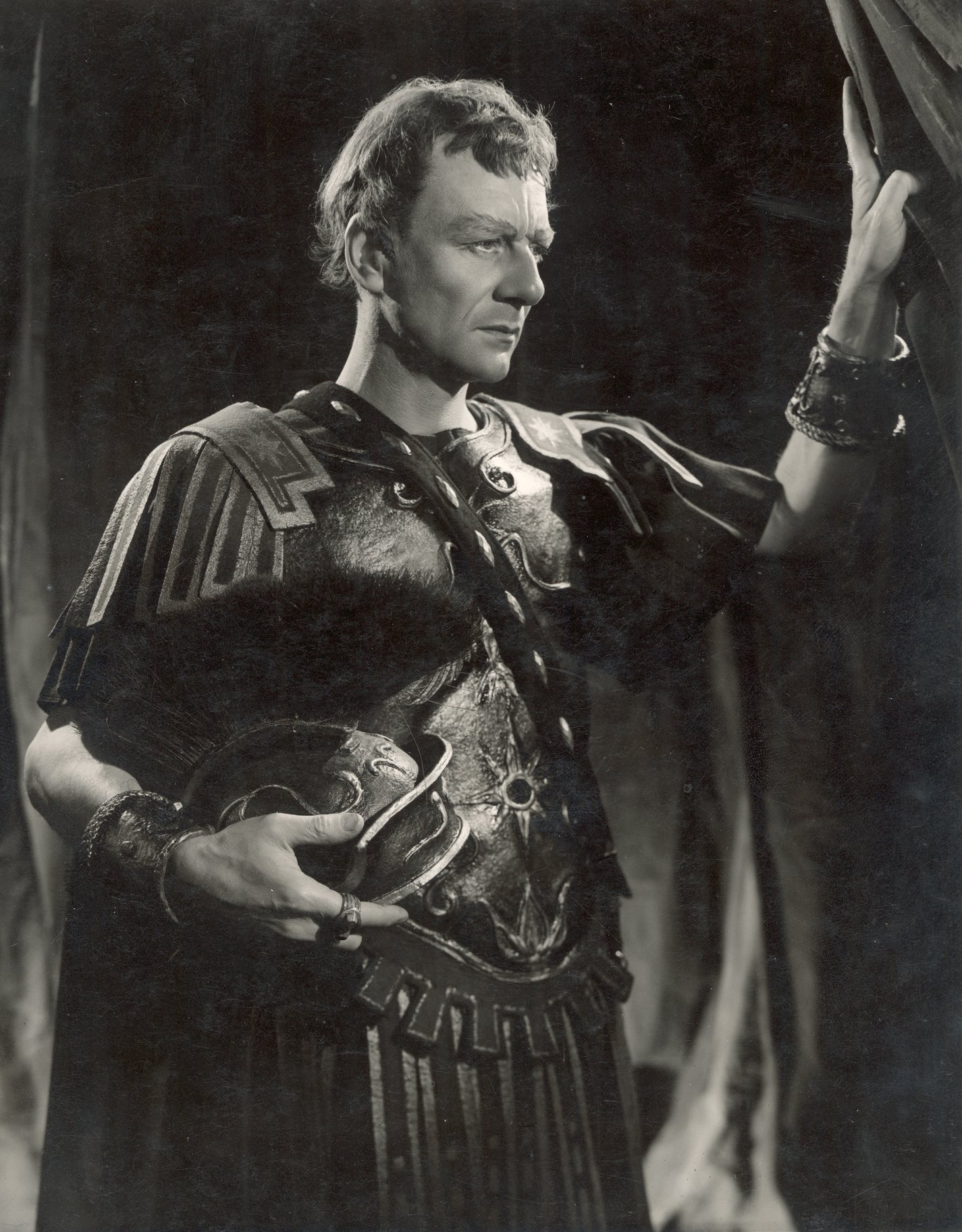 John Gielgus as Cassius, looking to the left, standing holding a helmet under his right arm