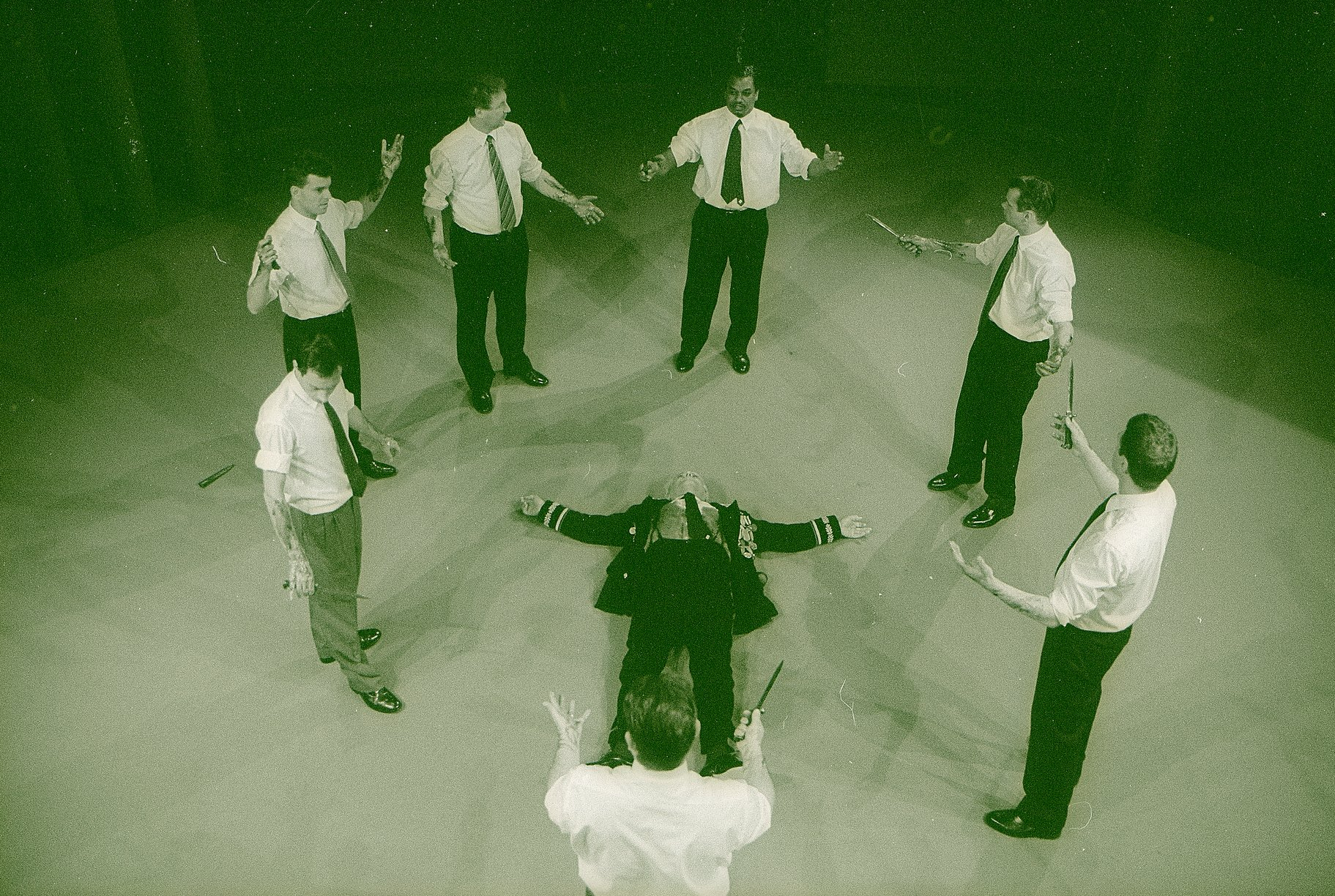 Six Conspirators stand in a circle around Julius Caesar's dead body
