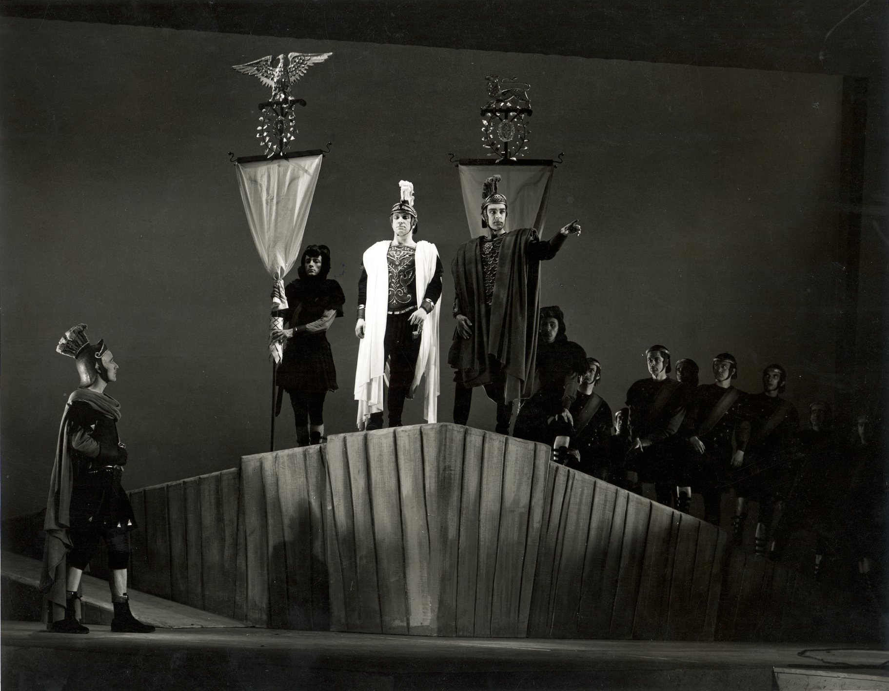 Octavius and Mark Antony stand at the edge of a platform with their troops at their backs in the 1957 production of Julius Caesar.
