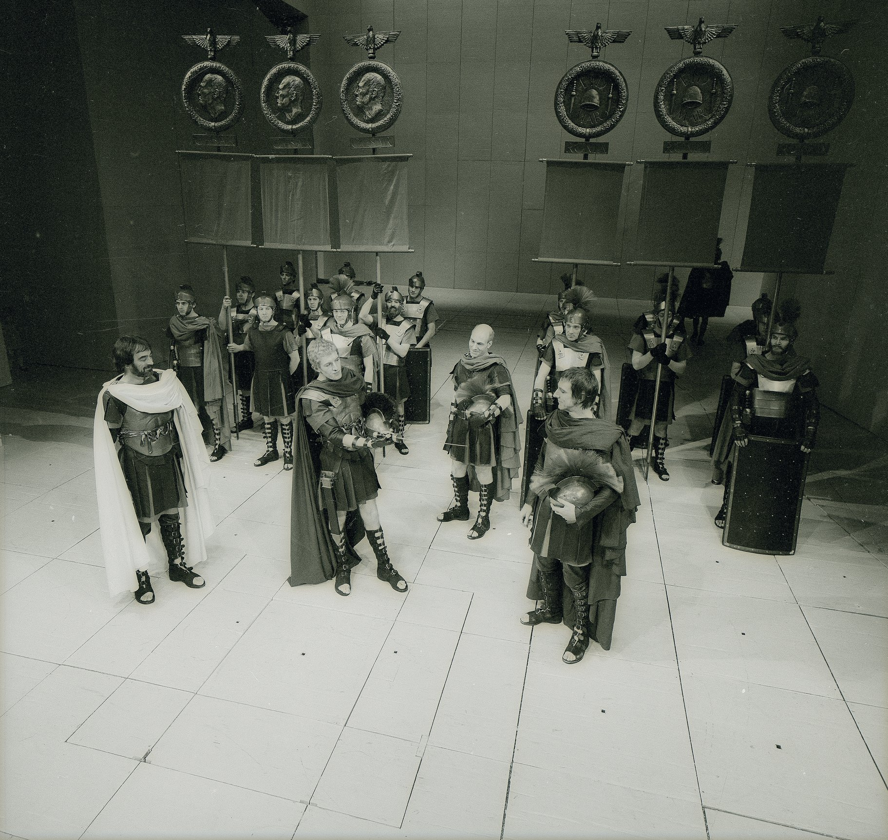 Roman Soldiers stand in formation upstage. Octavius, Lepidus and Mark Antony soldiers stand in discussion downstage