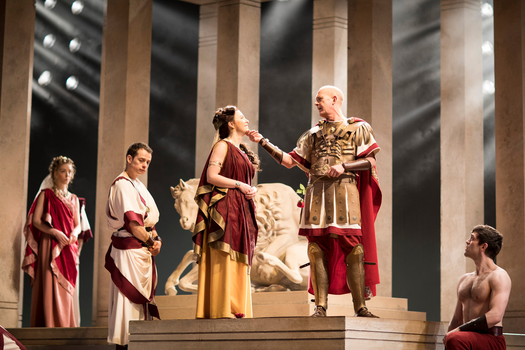 Julius Caesar stands next to Calphurnia with his hand on the underside of her chin. Portia, Brutus and Mark Antony observe.