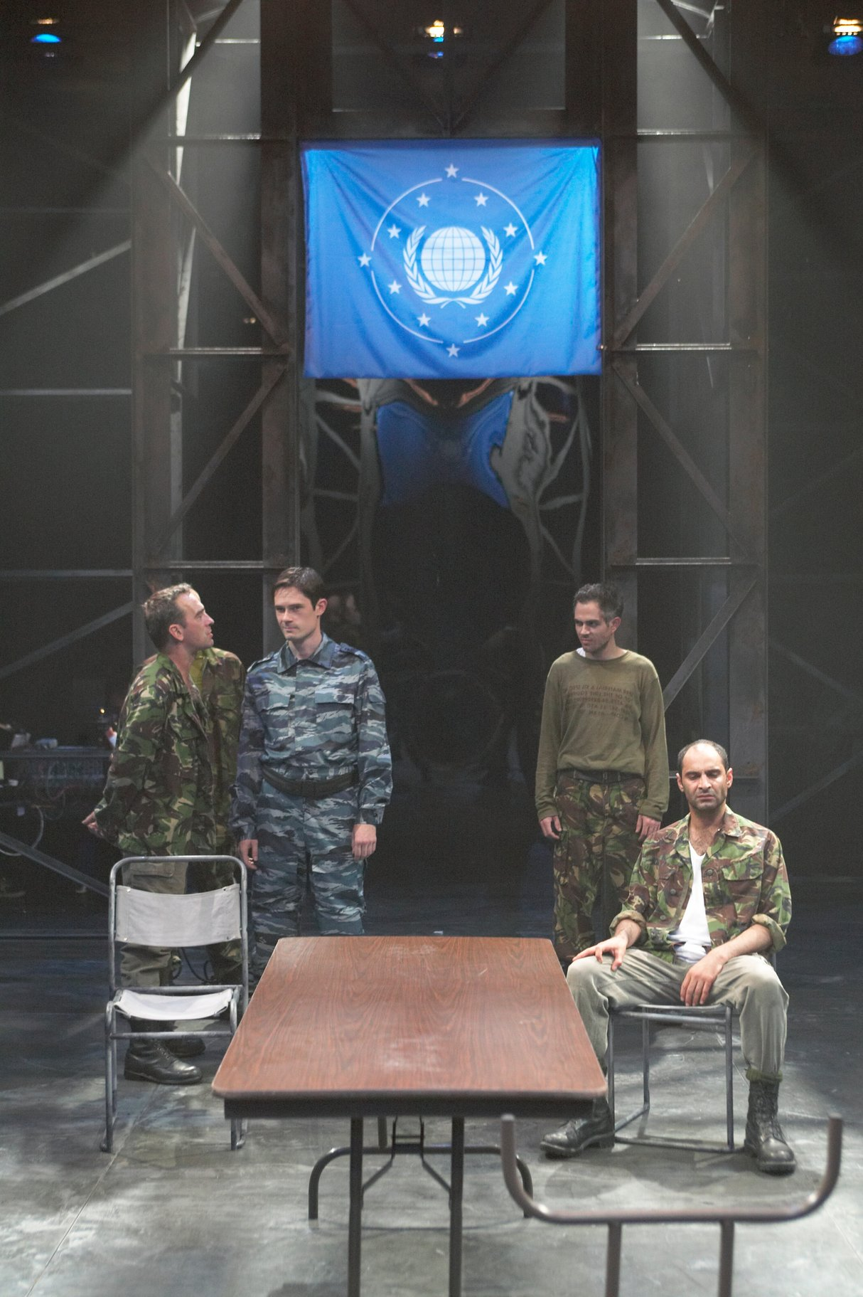 Cassius, Brutus, Cinna and Octavius meet at a large table with the symbol of the republic above them on a blue flag. They are all dressed in combat clothing in the 2004 production of Julius Caesar.