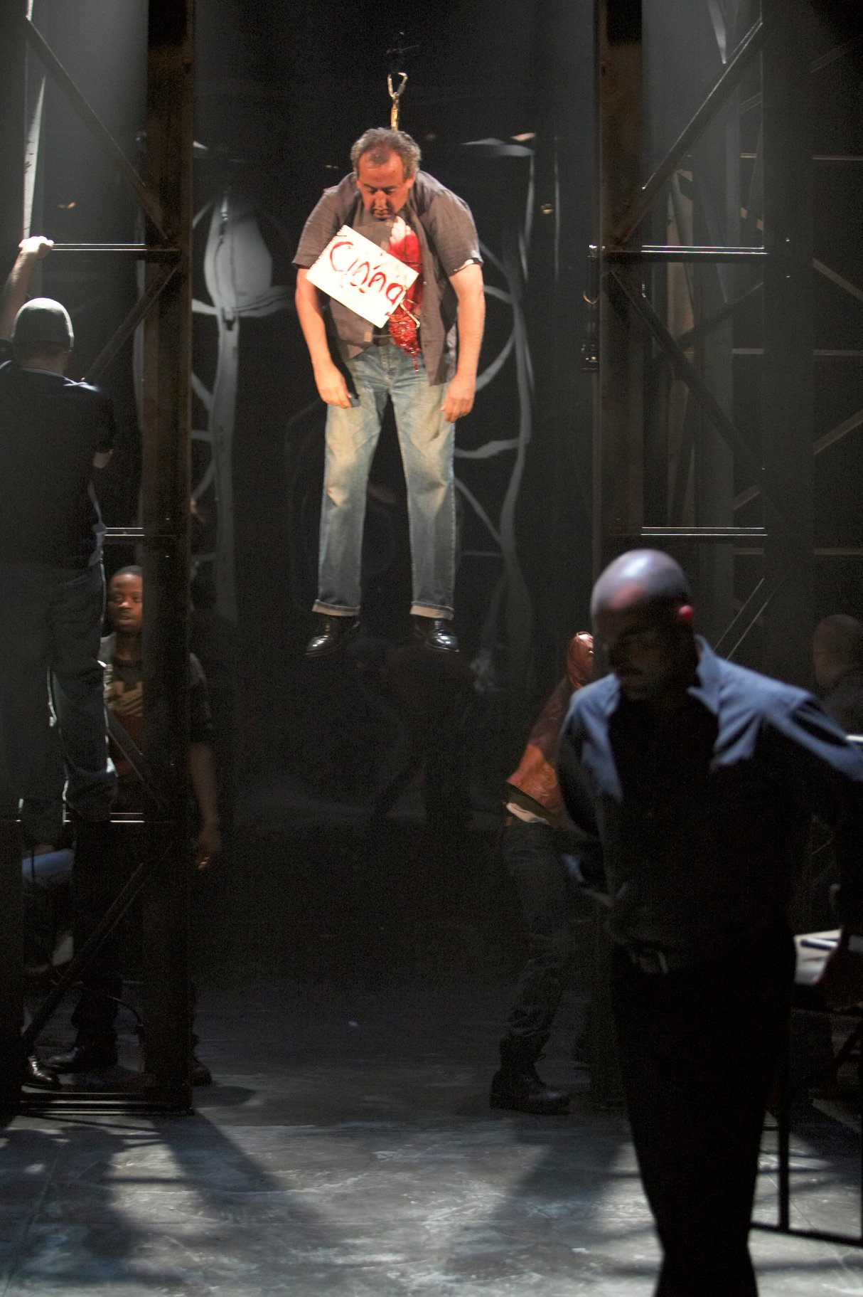 ​Cinna the poet hangs dead with a sign around his neck in the 2004 production of Julius Caesar.