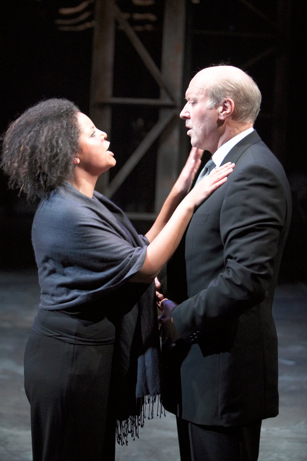 ​Calphurnia stands with her hands on Caesar's chest, both dressed in black, in the 2004 production of Julius Caesar.