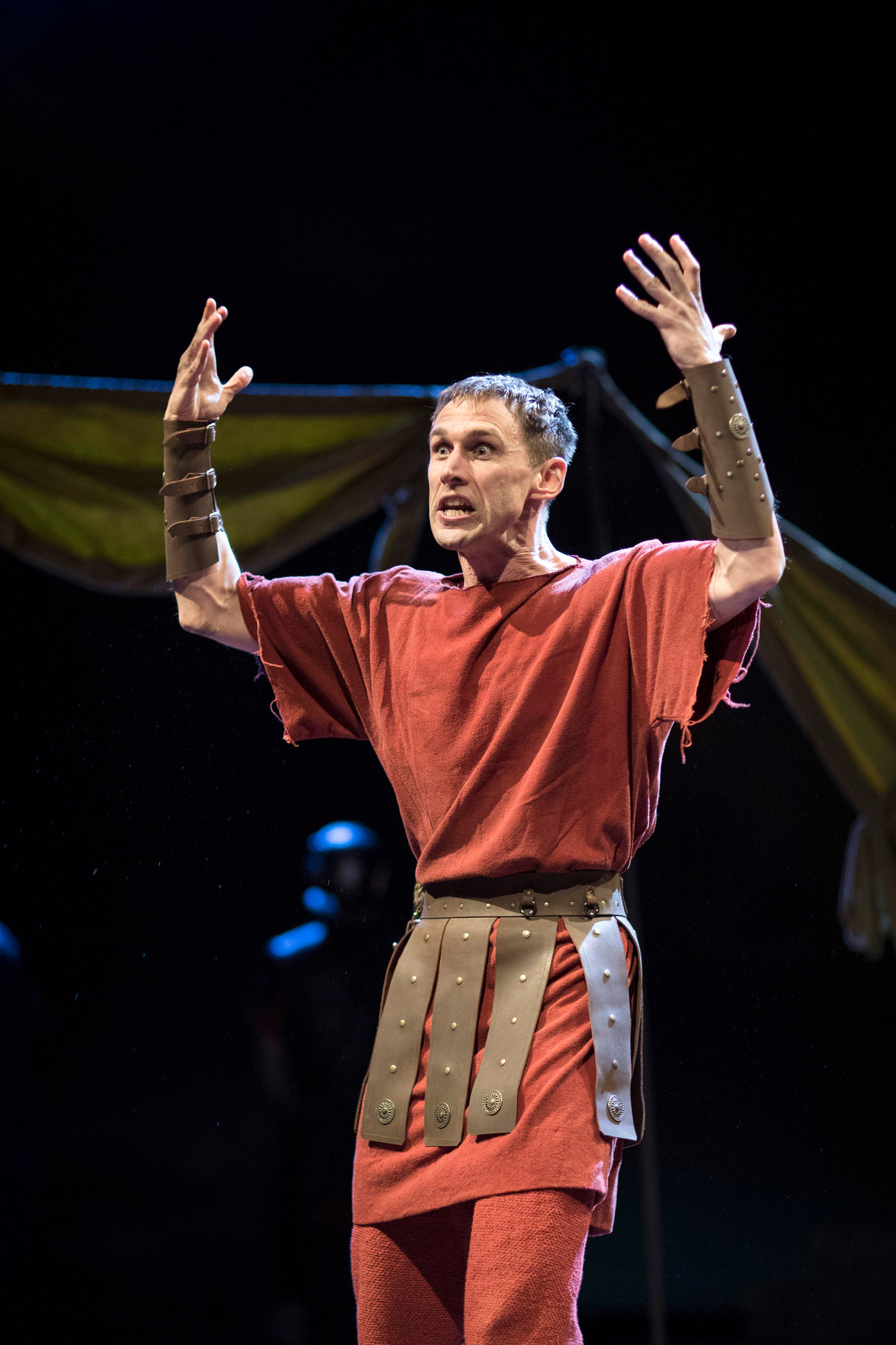 Cassius stands in uniform with his arms in the air in the 2017 production of Julius Caesar.