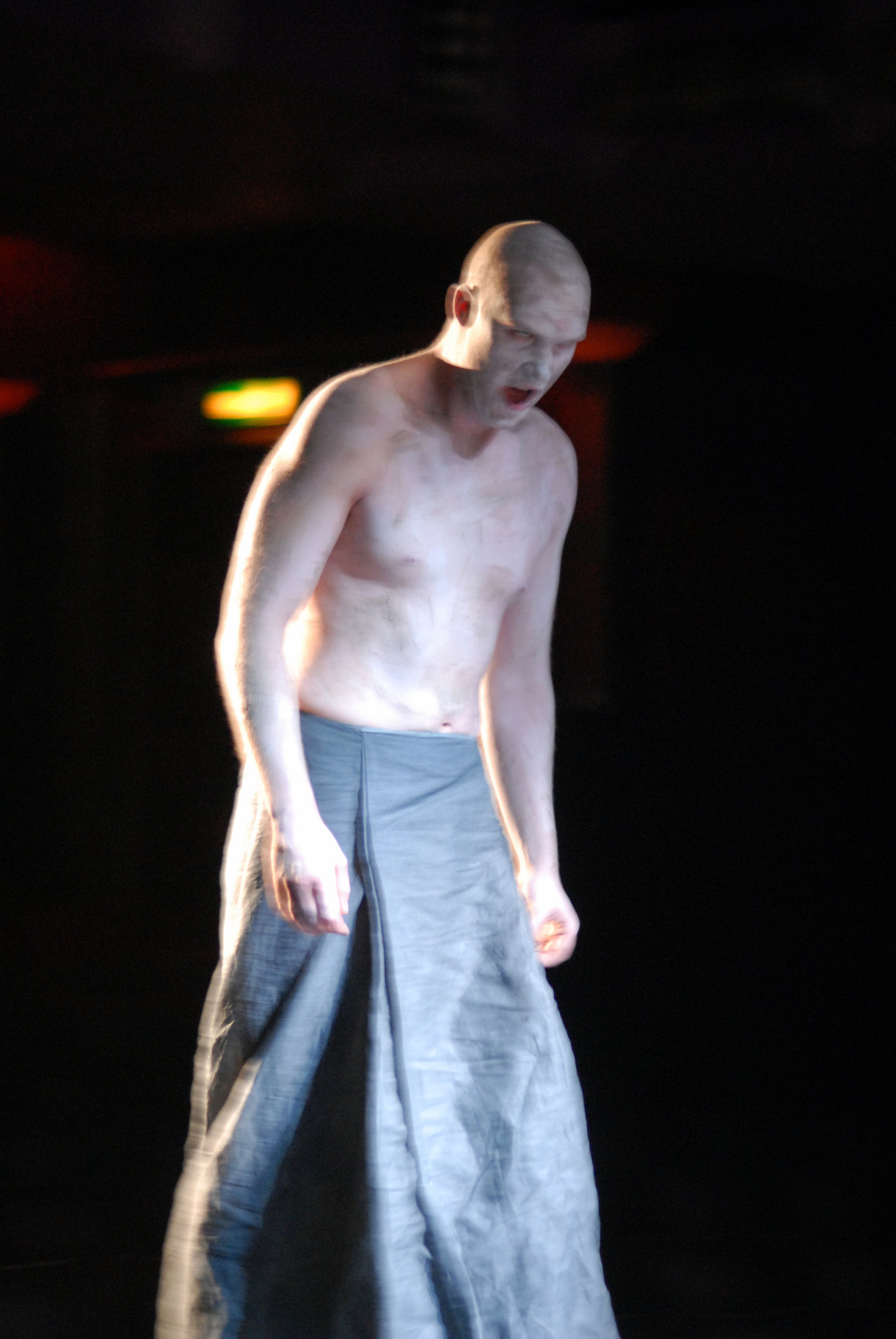 The soothsayer dressed in a grey lose fitting skirt with bare chest and covered in white paint in the 2006 production of Julius Caesar.