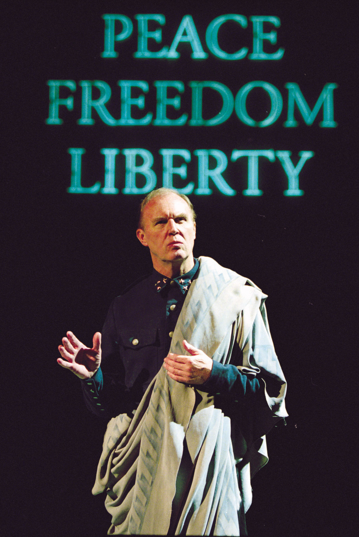 Cassius stands in front a sign reading 'Peace, Liberty, Freedom' in the 2001 production of Julius Caesar.