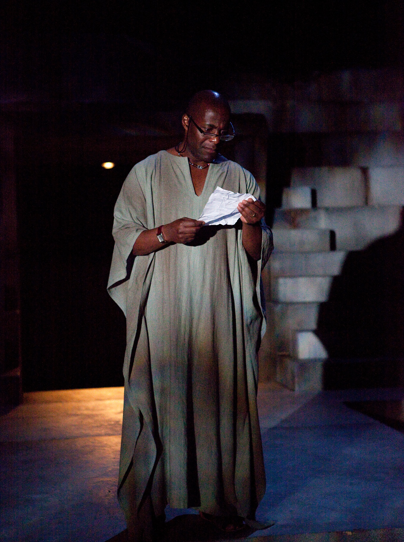 Brutus reading a letter with glasses on in the 2012 production of Julius Caesar.