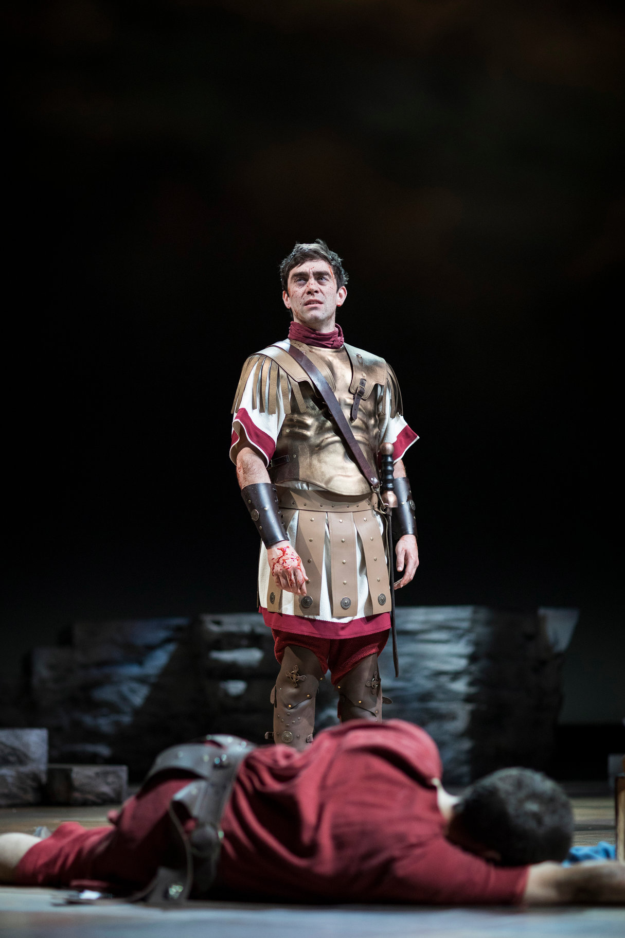 Mark Antony dressed in uniform stands over the dead body of Brutus in the 2017 production of Julius Caesar.