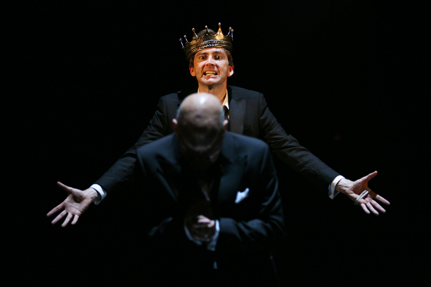 Hamlet stands behind Claudius as he prays.