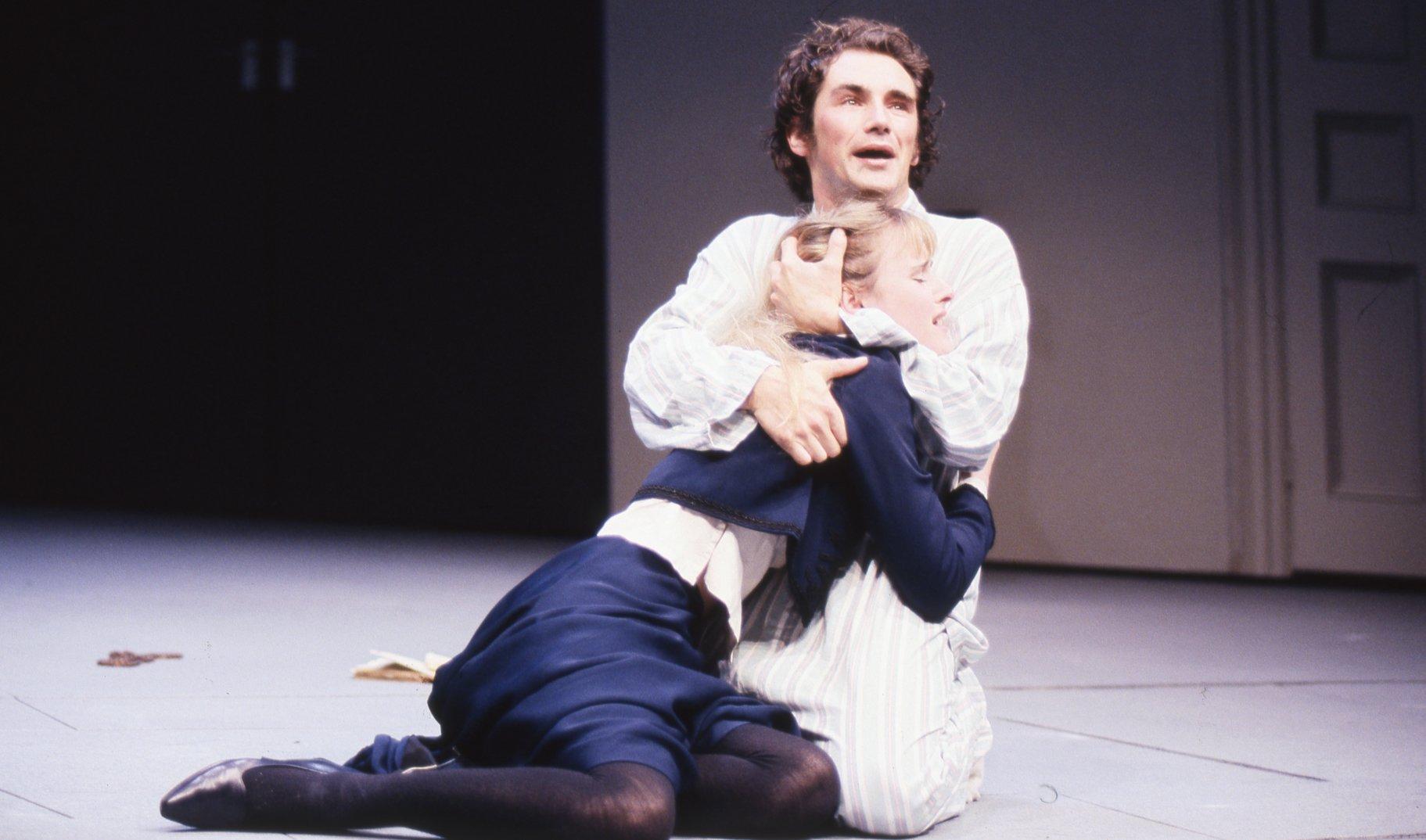 Hamlet embraces Ophelia.