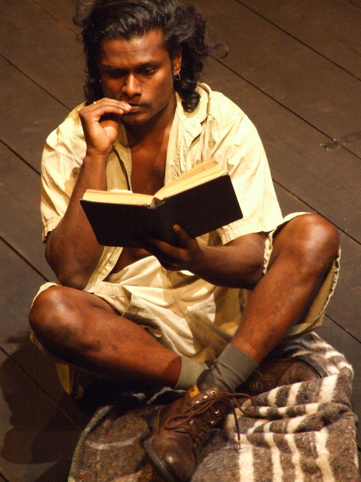 Hamlet sits cross-legged, reading a book.