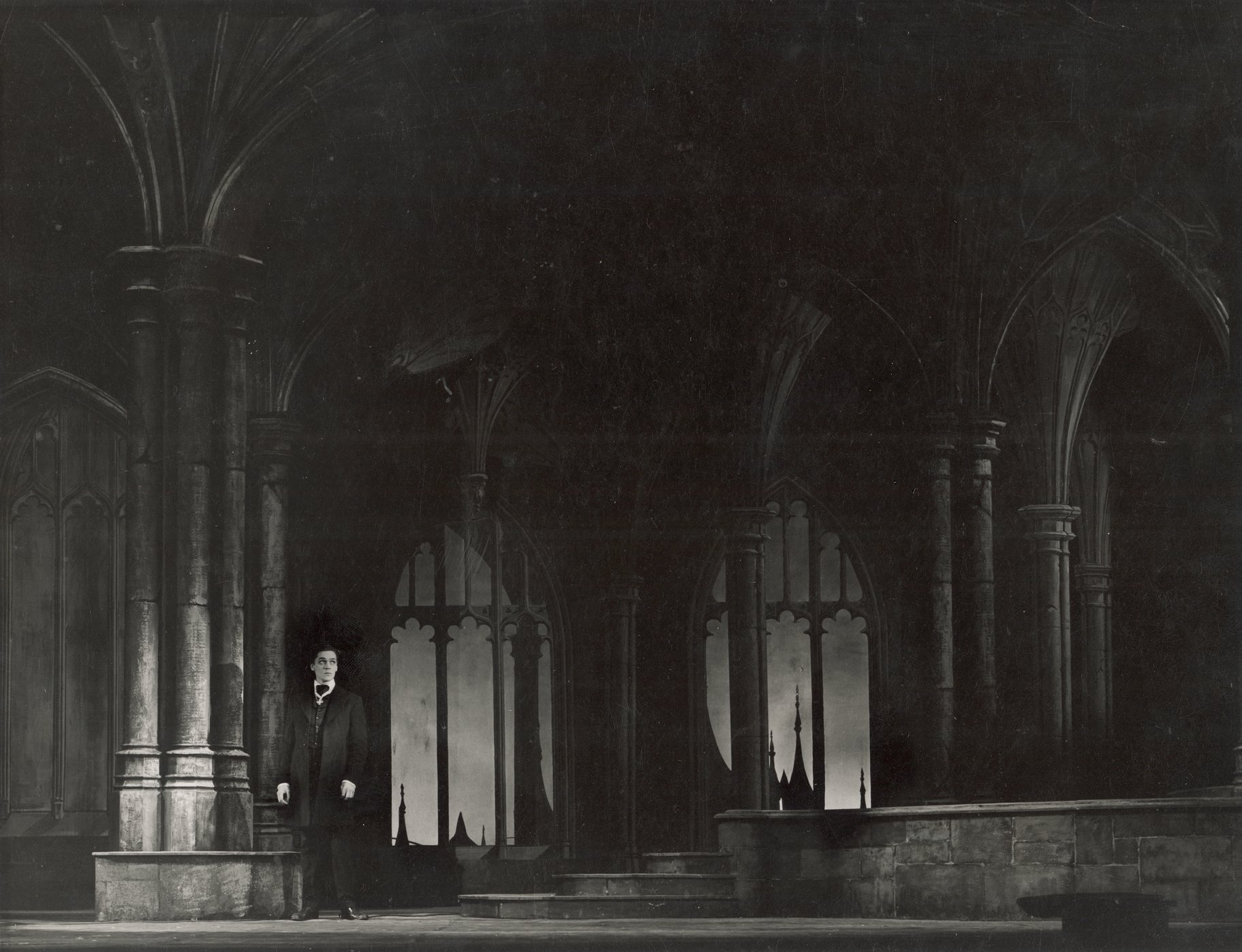 Hamlet stands alone in an old building with tall arches.