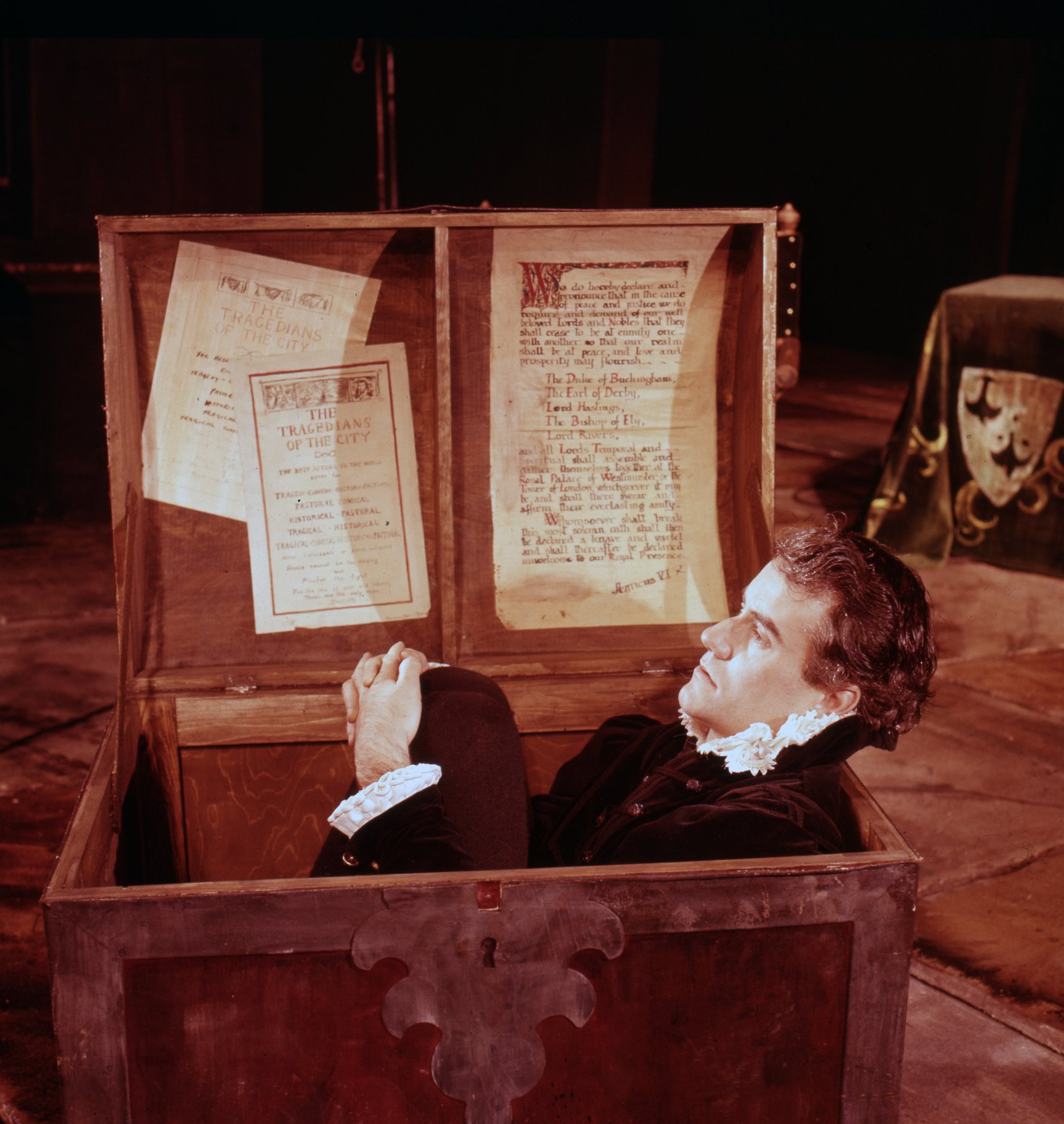 Ian Bannen as Hamlet, sitting in a wooden chest.