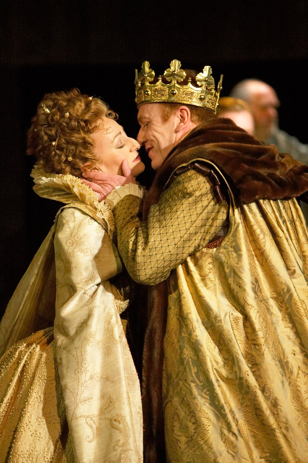 Gertrude and Claudius, both dressed in gold, lean in to kiss.