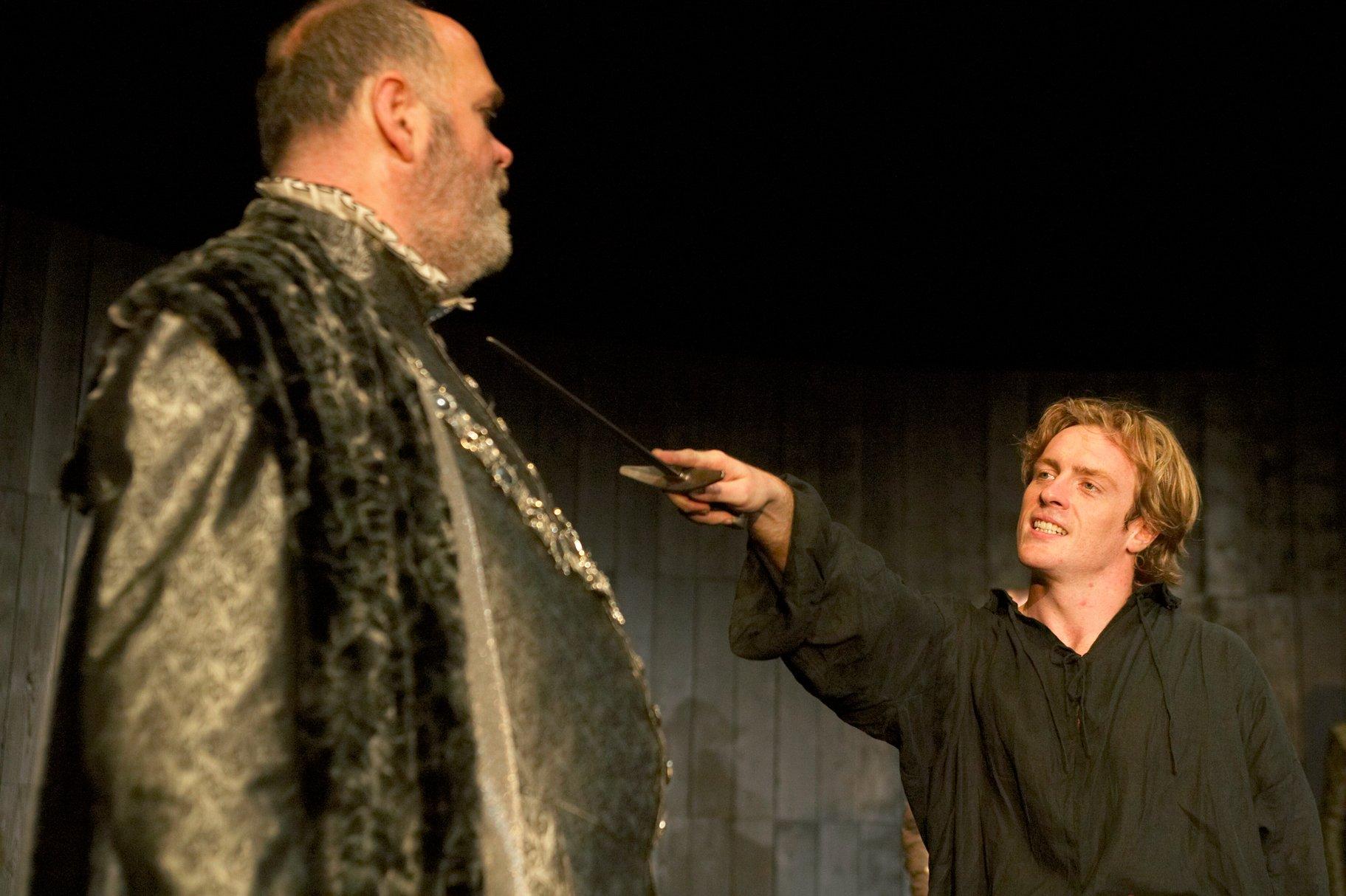 Hamlet holds a sword to Polonius' throat.