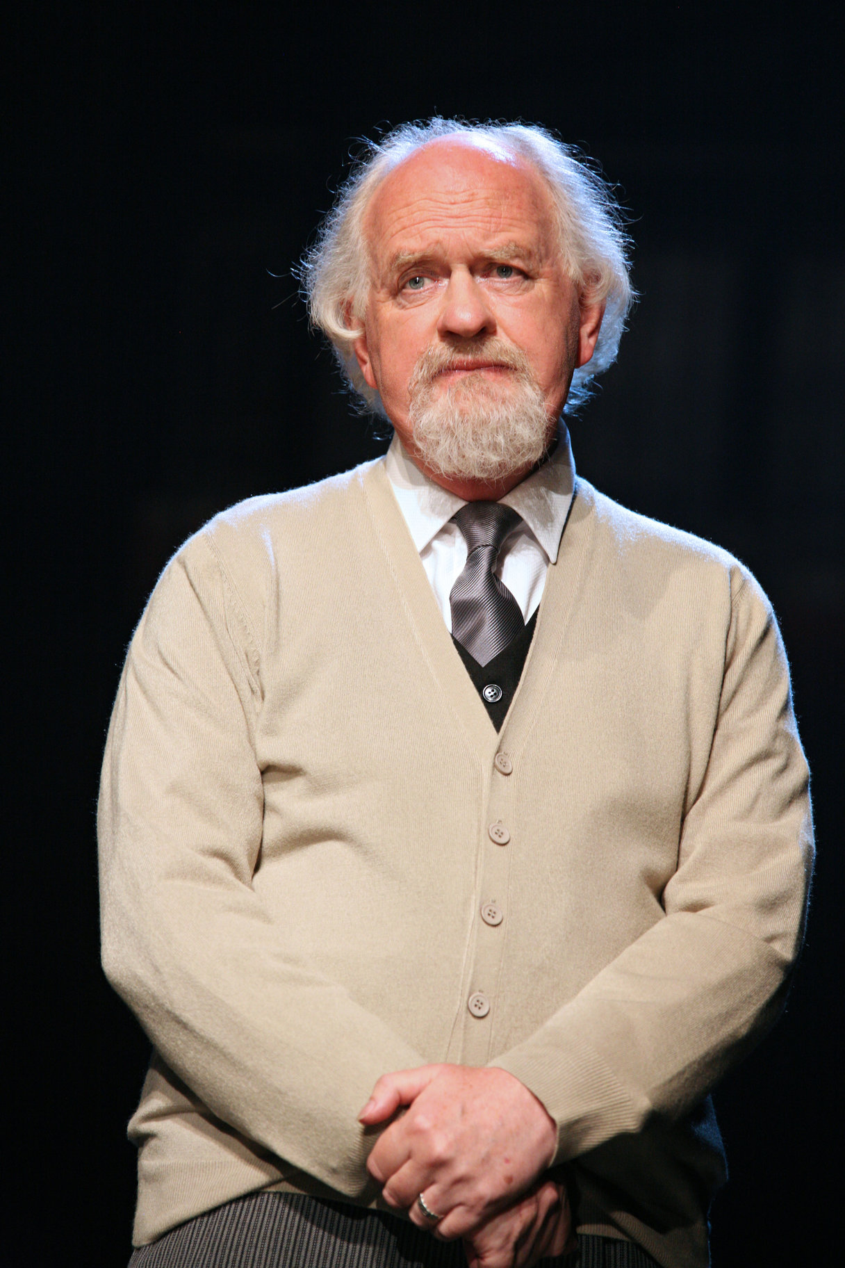 Polonius in a grey cardigan.