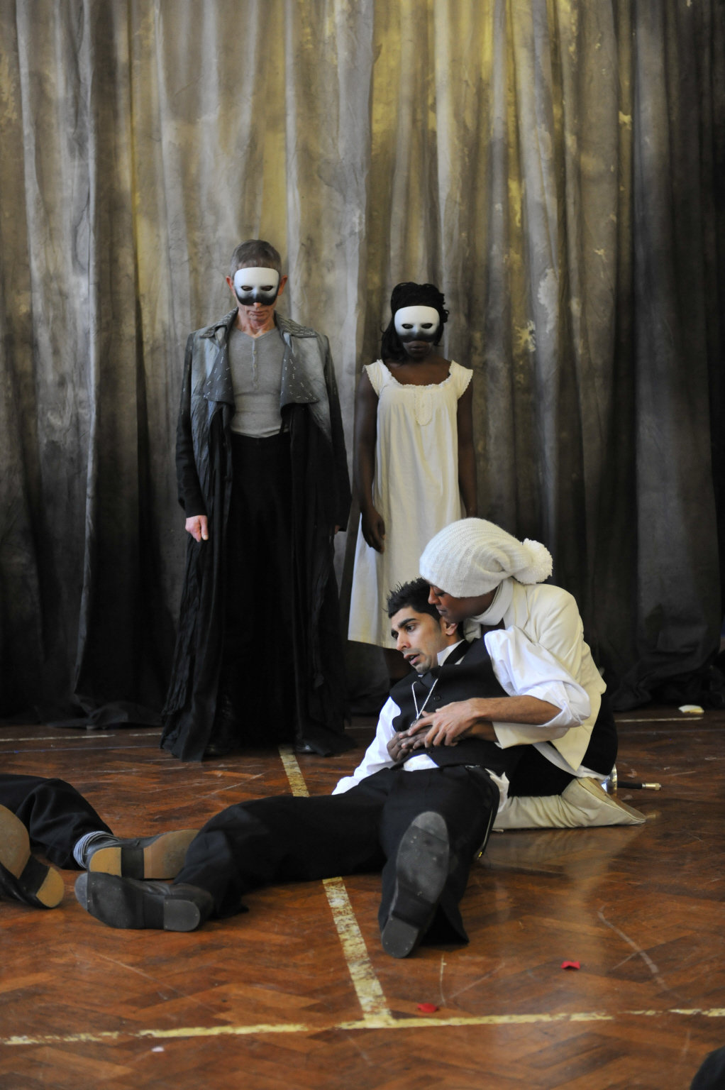 Hamlet dies, with the masked ghosts of his father and Ophelia behind him.