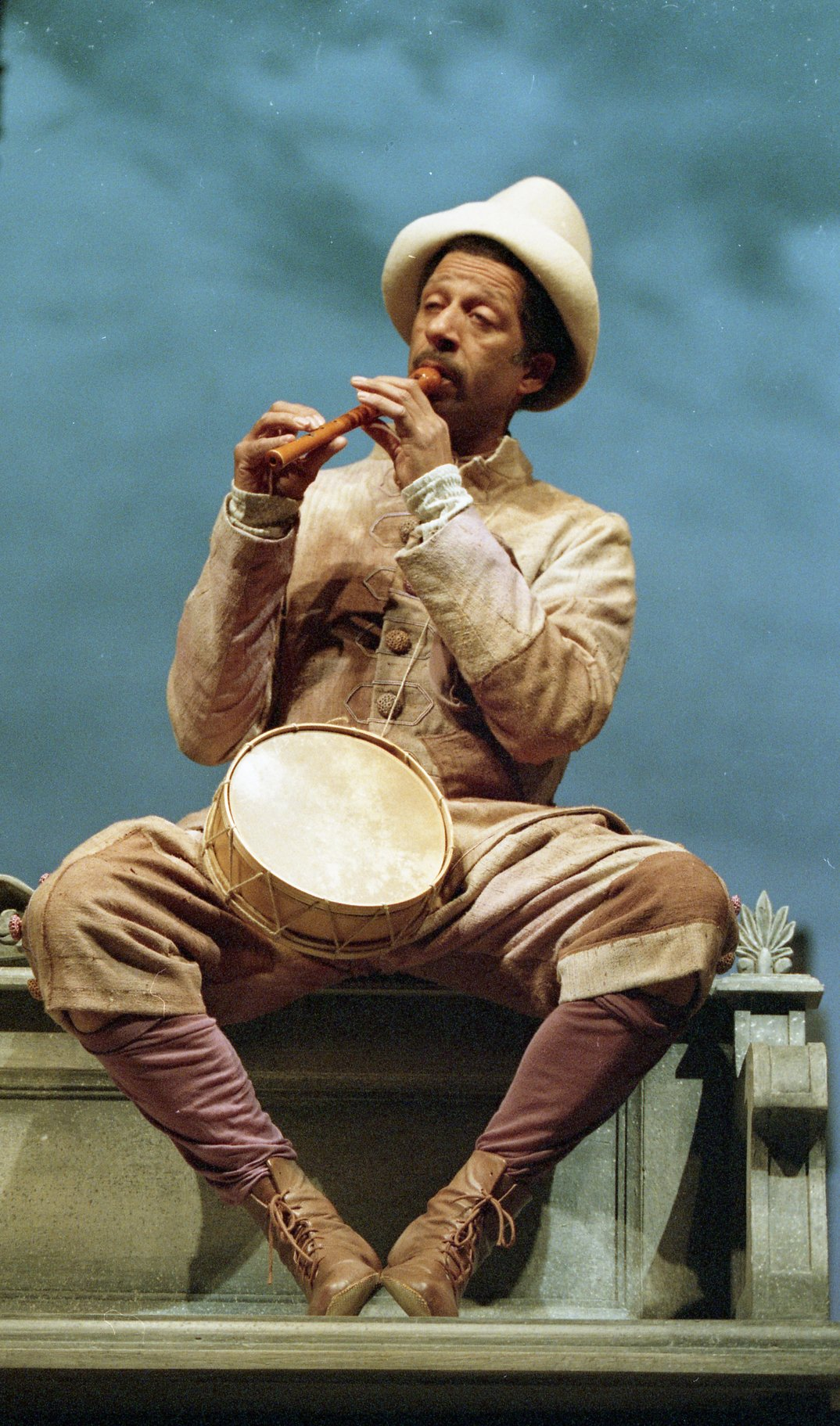 Feste sits, playing a pipe. A drum sits in his lap.