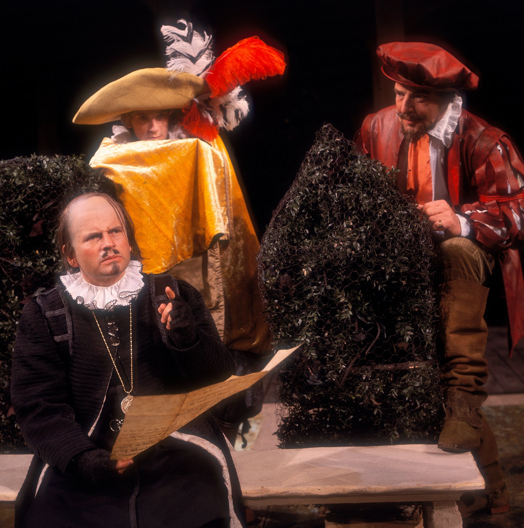 Malvolio sits on a bench dressed in black and is watched by Sir Toby and Sir Andrew who hide behind bushes behind him in the 1966 production of Twelfth Night.