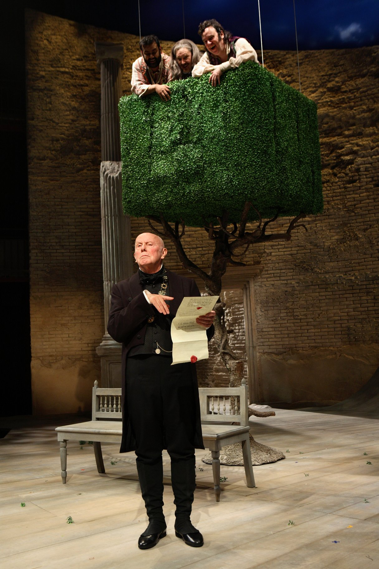 Malvolio stands and reads a letter in front of a large tree, wearing all black. He is watched by Sir Toby, Sir Andrew and Fabian who are all on top of the tress, looking down at him in the 2009 production of Twelfth Night.