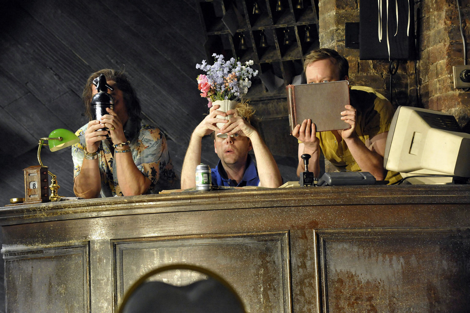 Sir Toby, Sir Andrew and Fabian hide from Malvolio behind an old bar, holding up objects in front of their faces in the 2012 production of Twelfth Night.