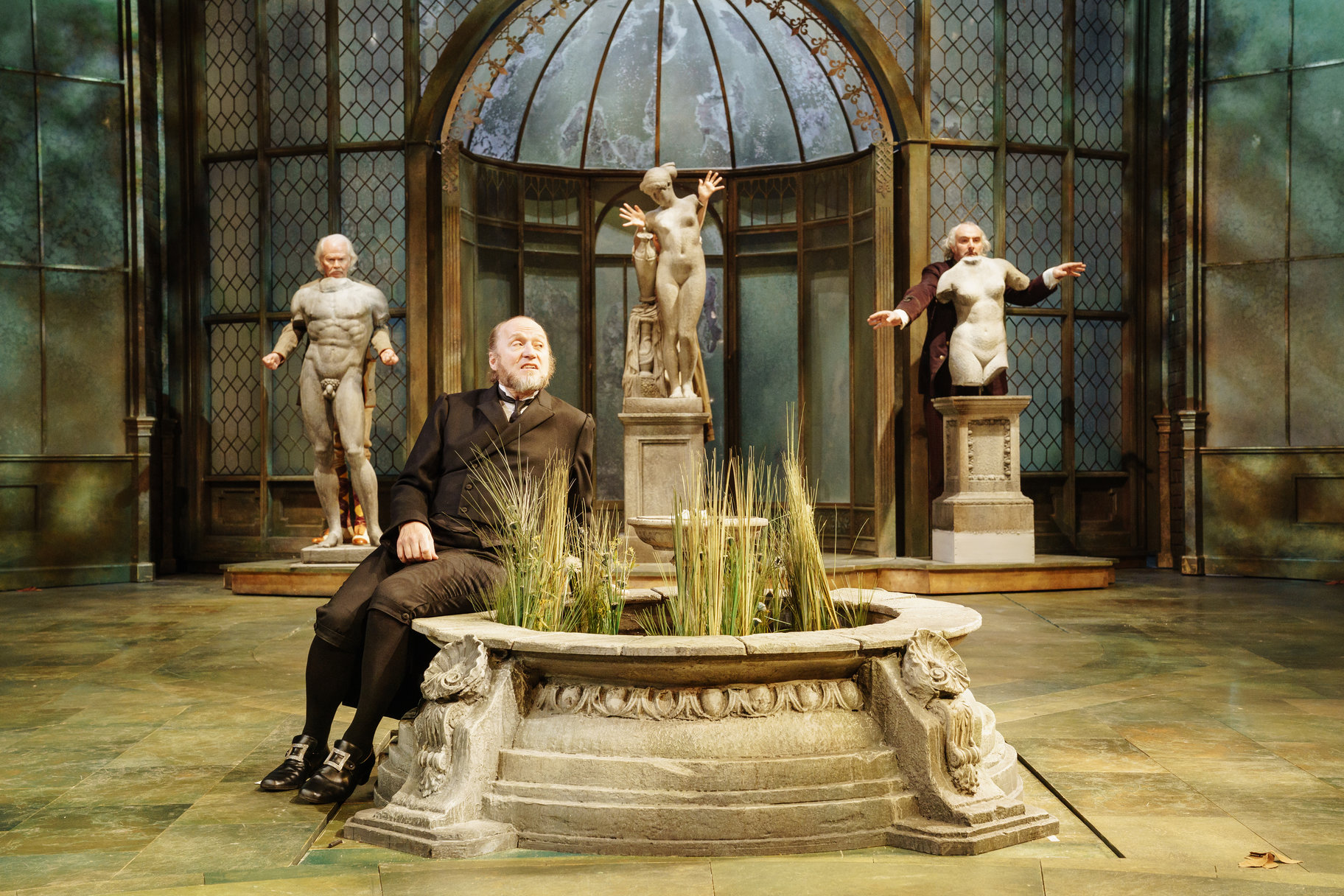Malvolio sits on the edge of a stone flower bed in a conservatory wearing a butler's uniform. He is watched by Sir Toby, Sir Andrew and Fabia who all hide behind old and damaged statues in the 2017 production of Twelfth Night.