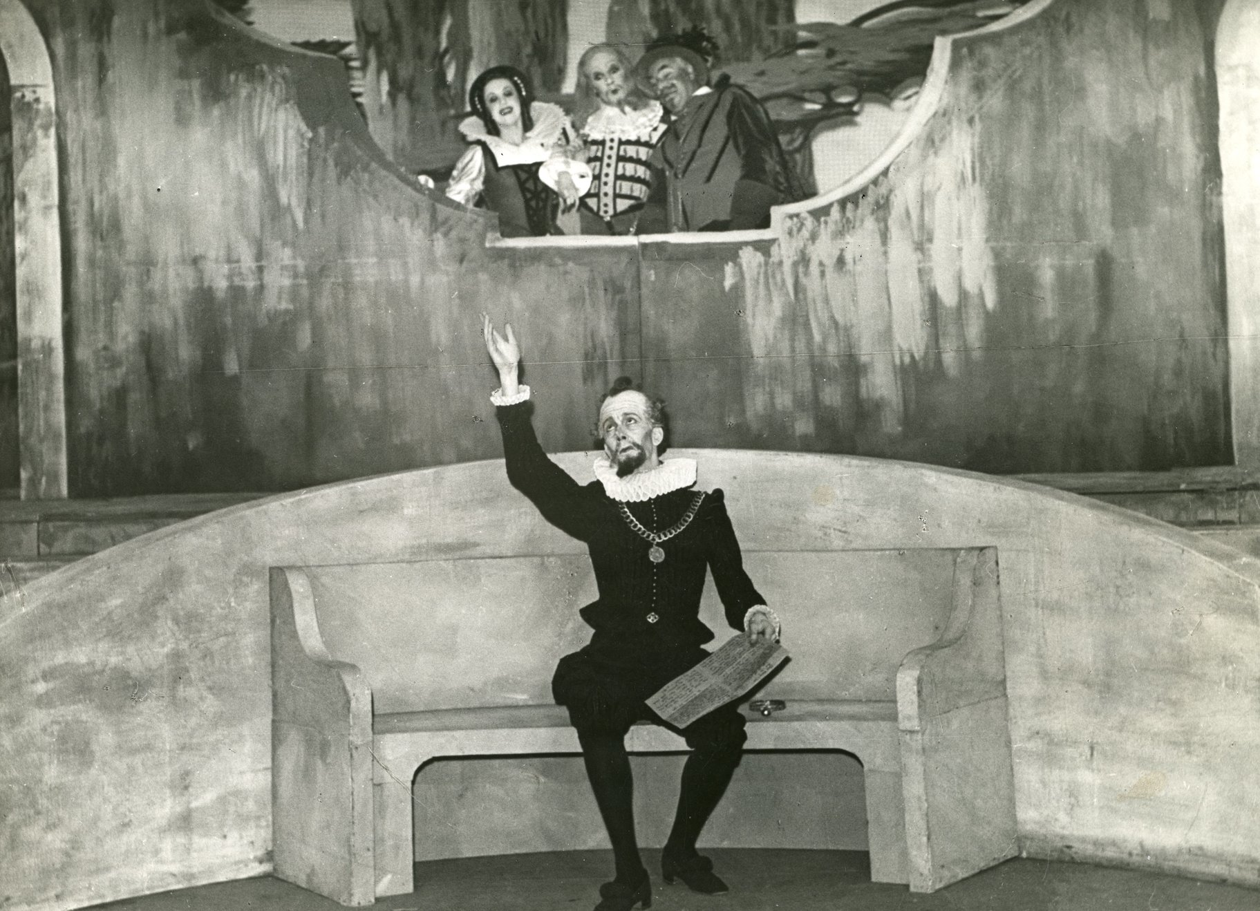 Malvolio sits on a bench wearing all black and reading a letter and is watched by Sir Toby, Sir Andrew and Maria from above in the 1945 production of Twelfth Night.