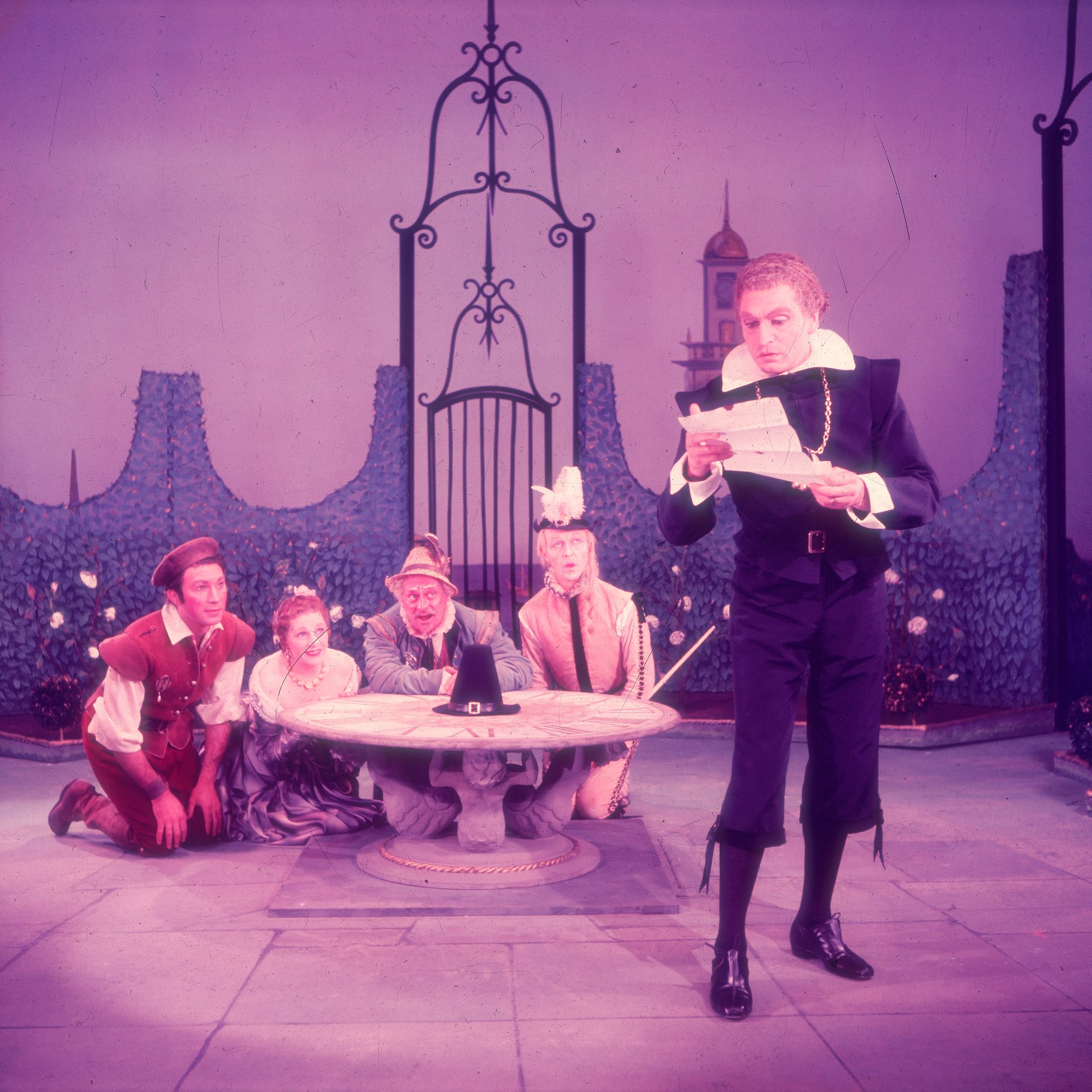 Malvolio is dressed in black with a chain round his neck and reading a letter while standing. He is watched by Sir Toby, Sir Andrew, Maria and Fabian who are all crouched behind a small garden table behind him in the 1955 production of Twelfth Night.