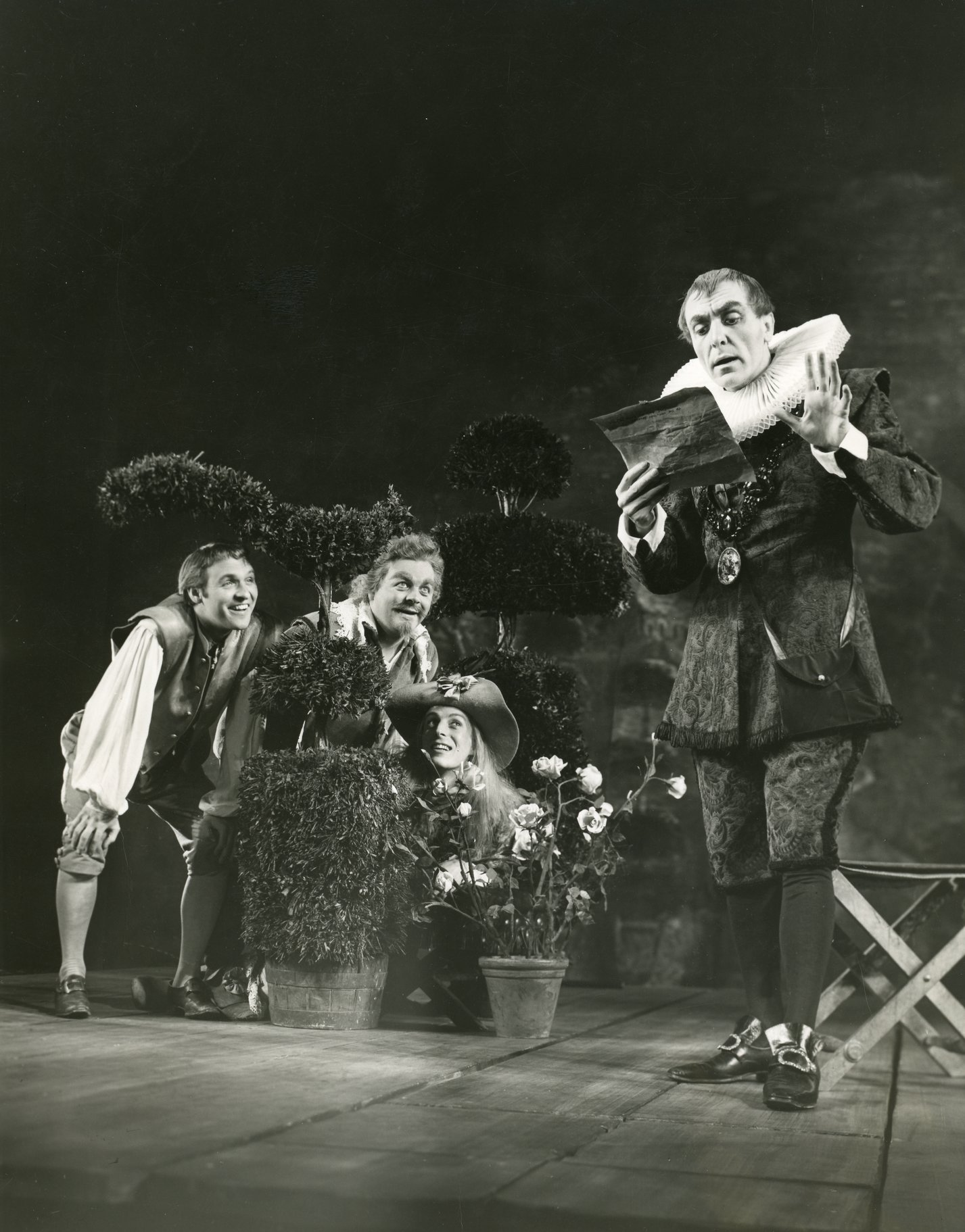Malvolio reads a letter while dressed in a dark doublet and white ruff. He is watched by Sir Toby, Sir Andrew and Fabian who hide behind small plat pots in the 1960 production of Twelfth Night.