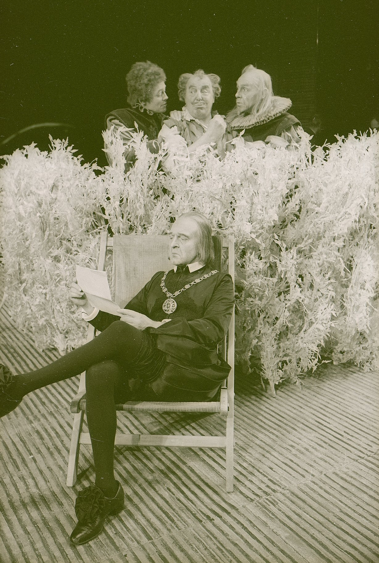 Malvolio sits cross legged in a garden chair reading a letter while dressed all in black with a large chain round his neck. He is watched by Sir Toby, Sir Andrew and Fabian who are hiding behind a large hedge in the 1969 production of Twelfth Night.