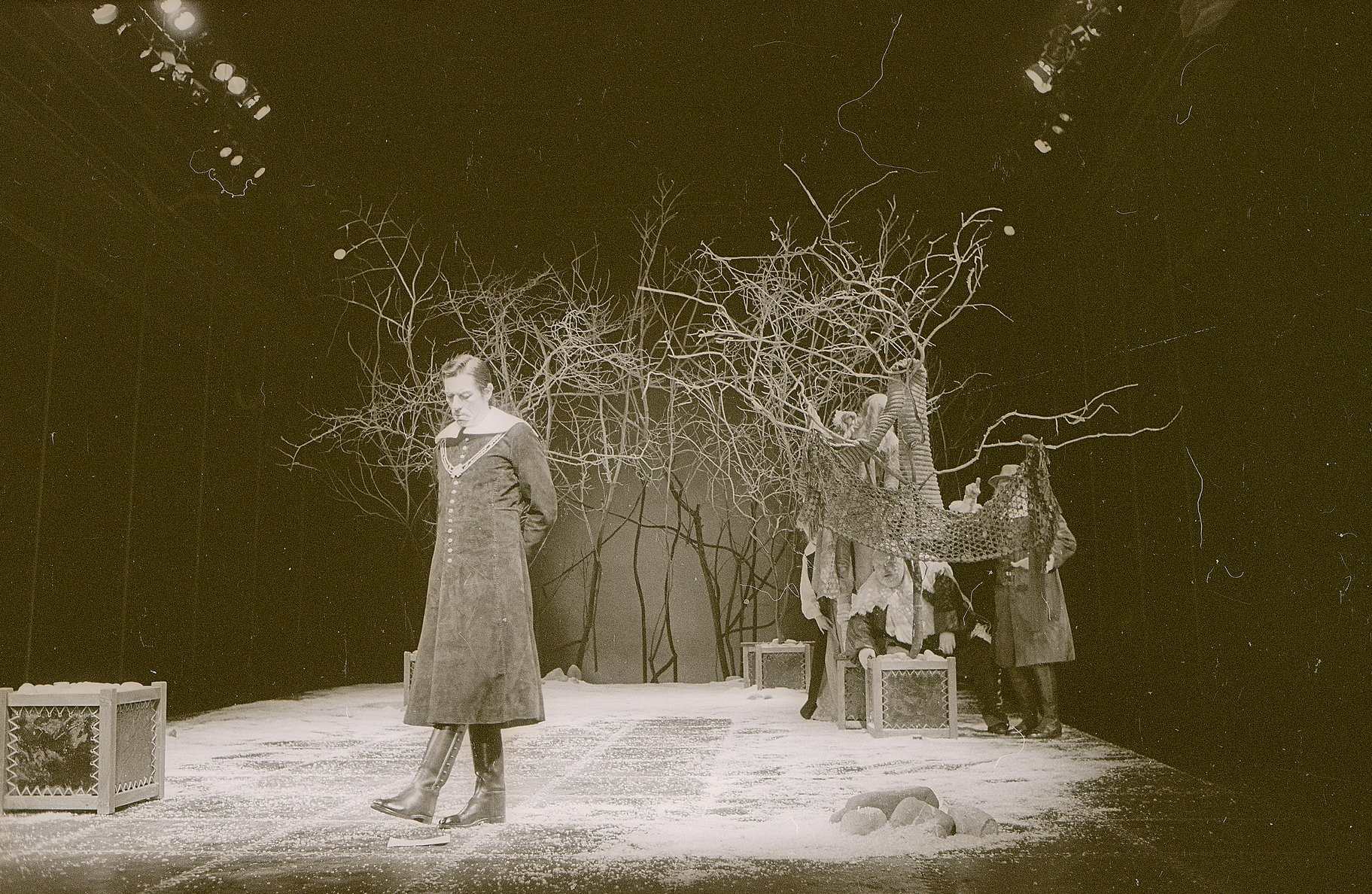 Malvolio paces up and down wearing a long plain coat and is watched by Sir Toby, Sir Andrew and Fabian who are hiding in some branches at the back of the stage in the 1979 production of Twelfth Night.