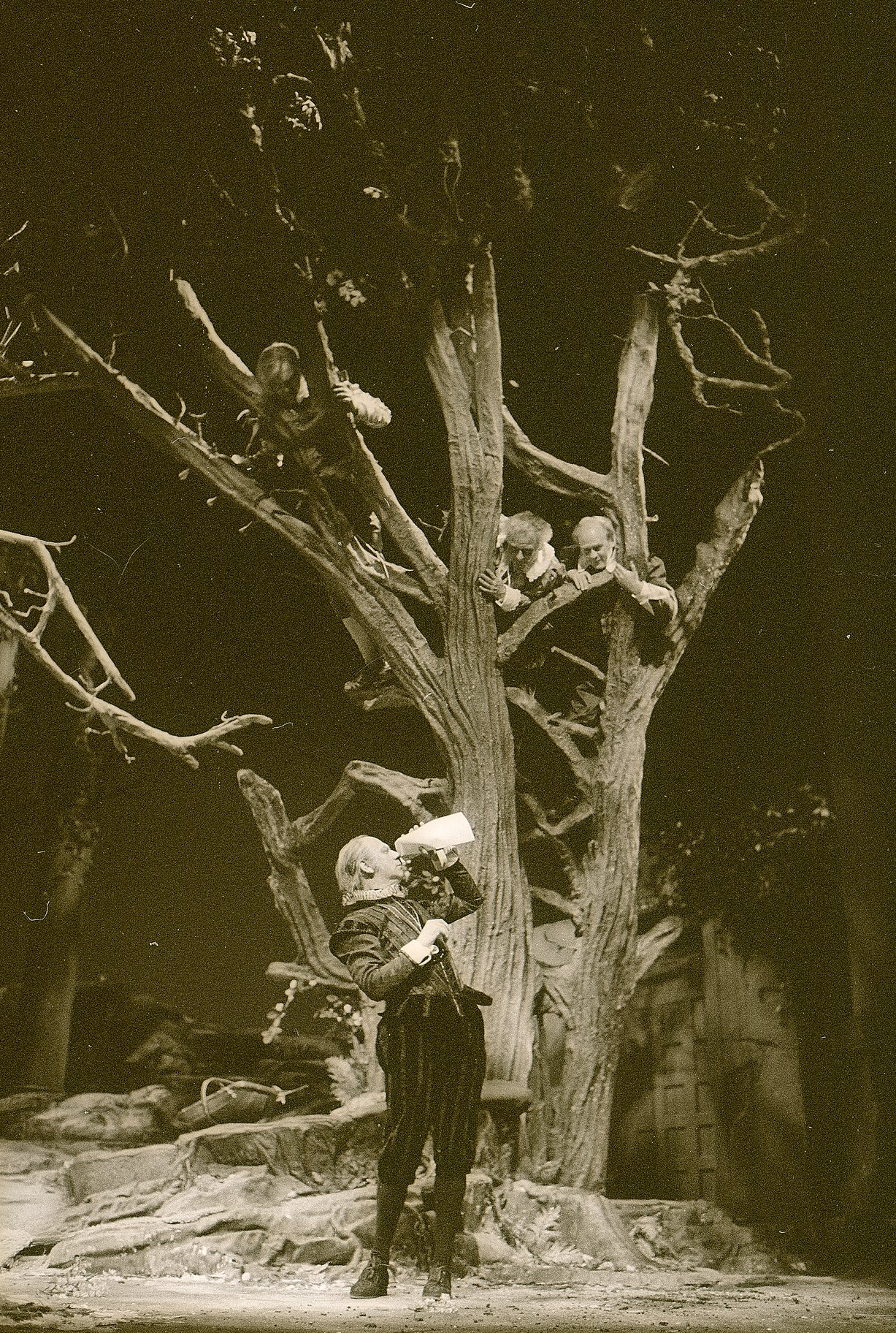 Malvolio inspects a letter while standing at the bottom of a tree in formal dress. He is watched by Sir Toby, Sir Andrew and Fabian who are all sitting in the branches of the tree in the 1983 production of Twelfth Night.