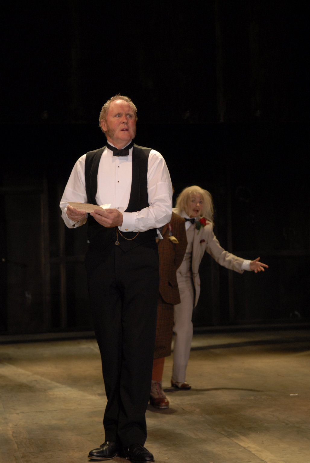 John Lithgow as Malvolio. He is standing reading a letter.