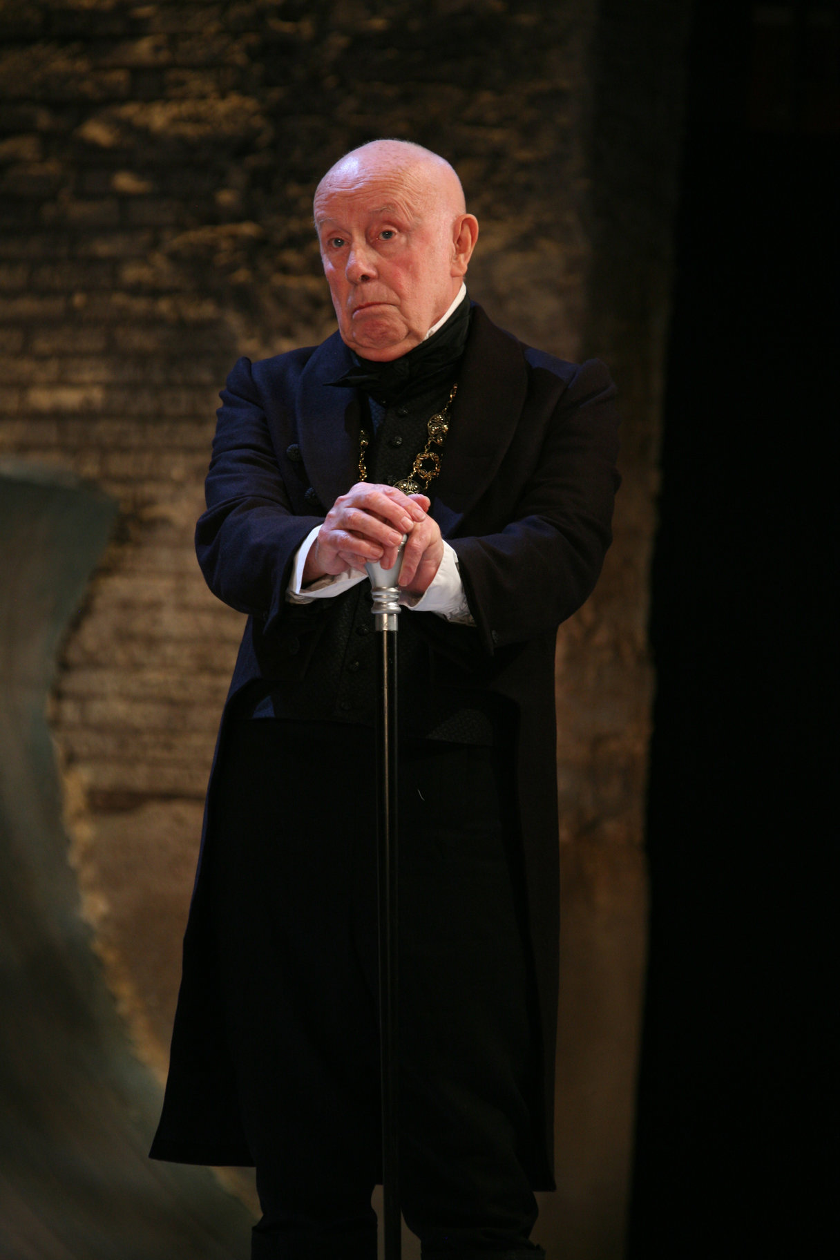 Richard Wilson as Malvolio. He is standing looking ahead, with his hands resting on the top of a cane.