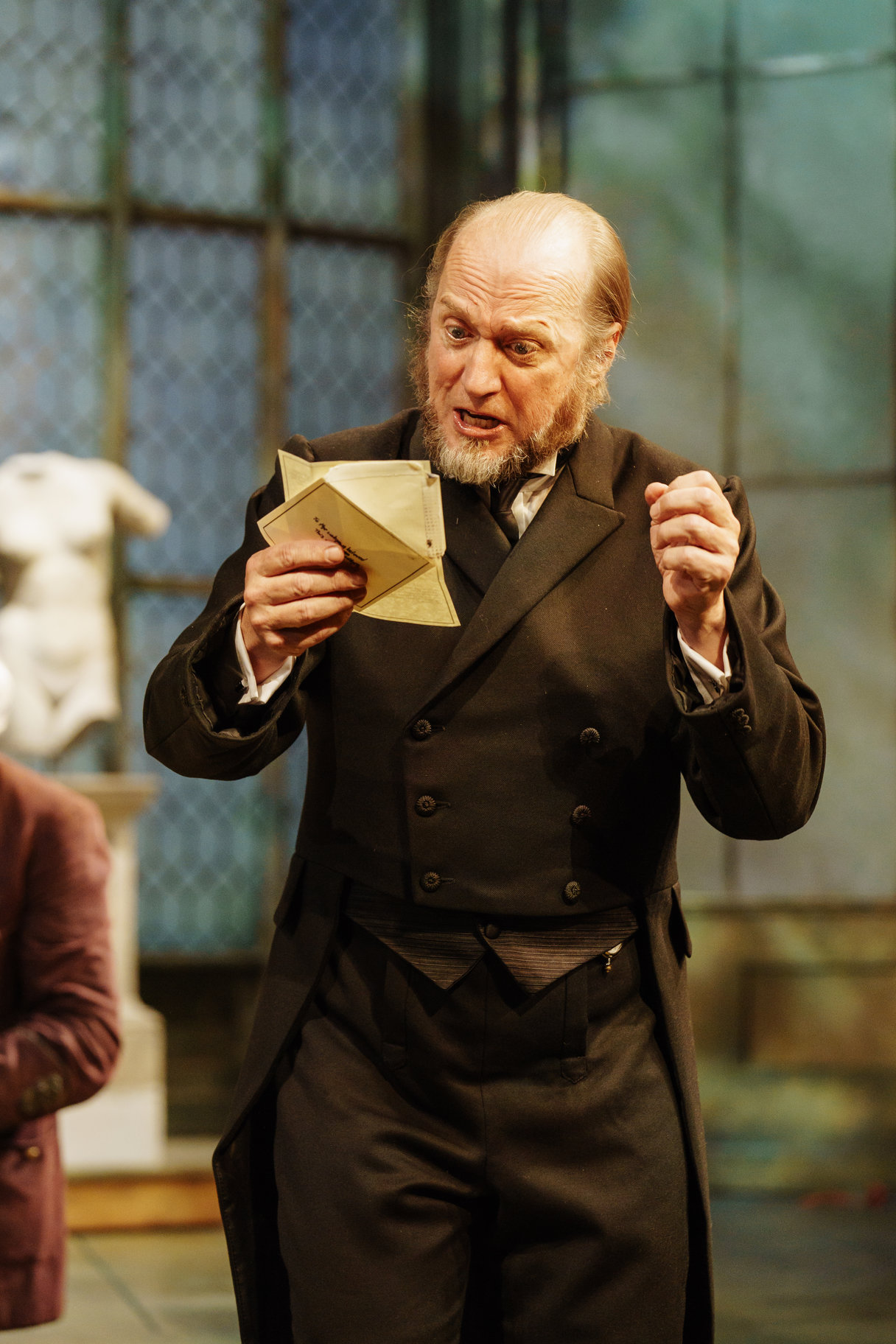 Ade Edmonson as Malvolio. He is standing reading a letter.