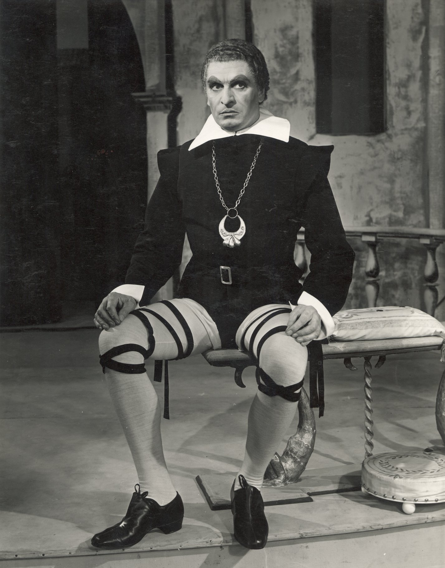 Malvolio sits , wearing cross-gartered stockings.
