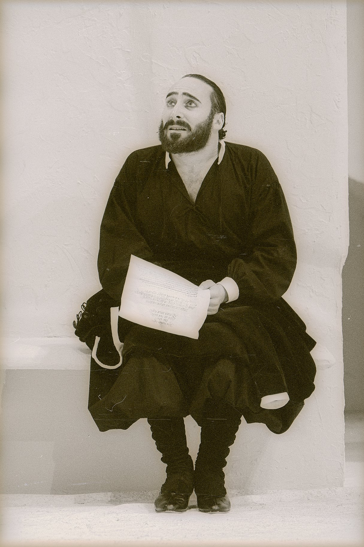 Malvolio sits looking upwards, holding a letter