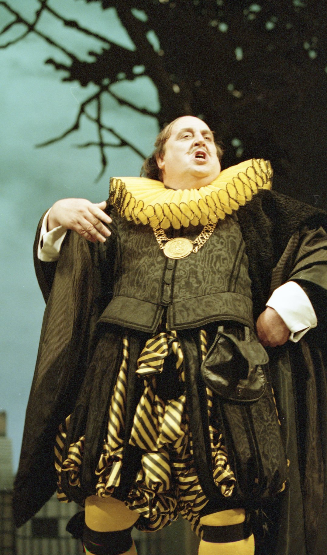 Malvolio standing in yellow stockings, with his left hand on his hip