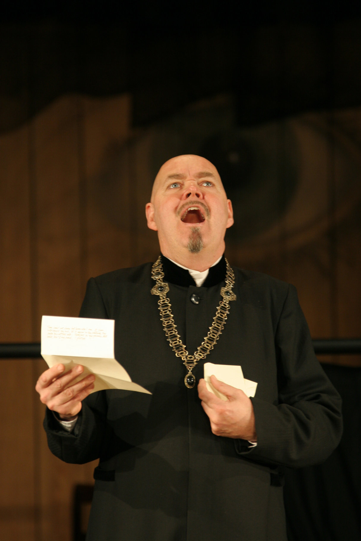 Malvolio looks upwards, with a letter in his right hand. He is mid-speech.