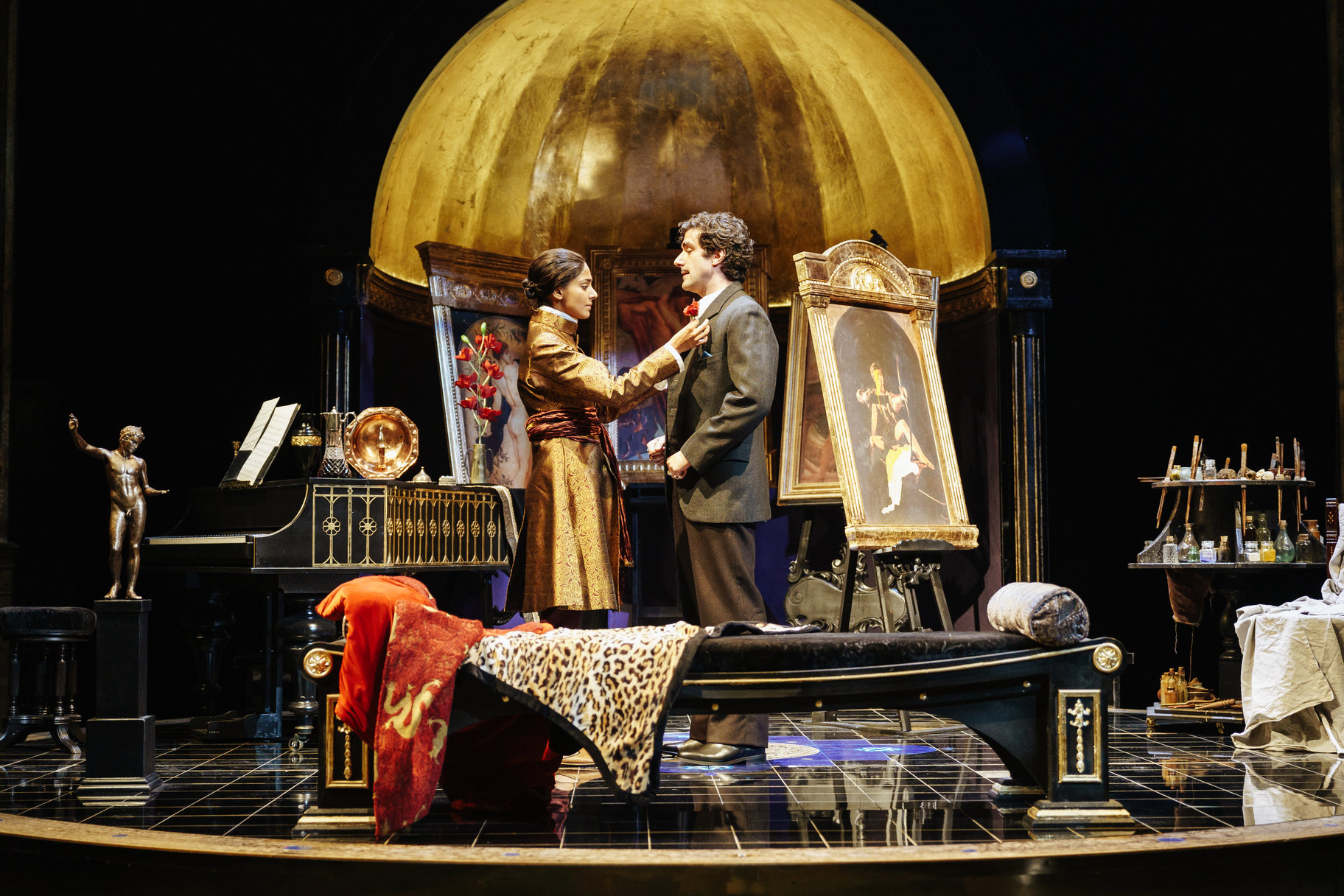 Viola straightens Orsino's lapels while they stand in his home in front of his art work and paint brushes in the 2017 production of Twelfth Night.