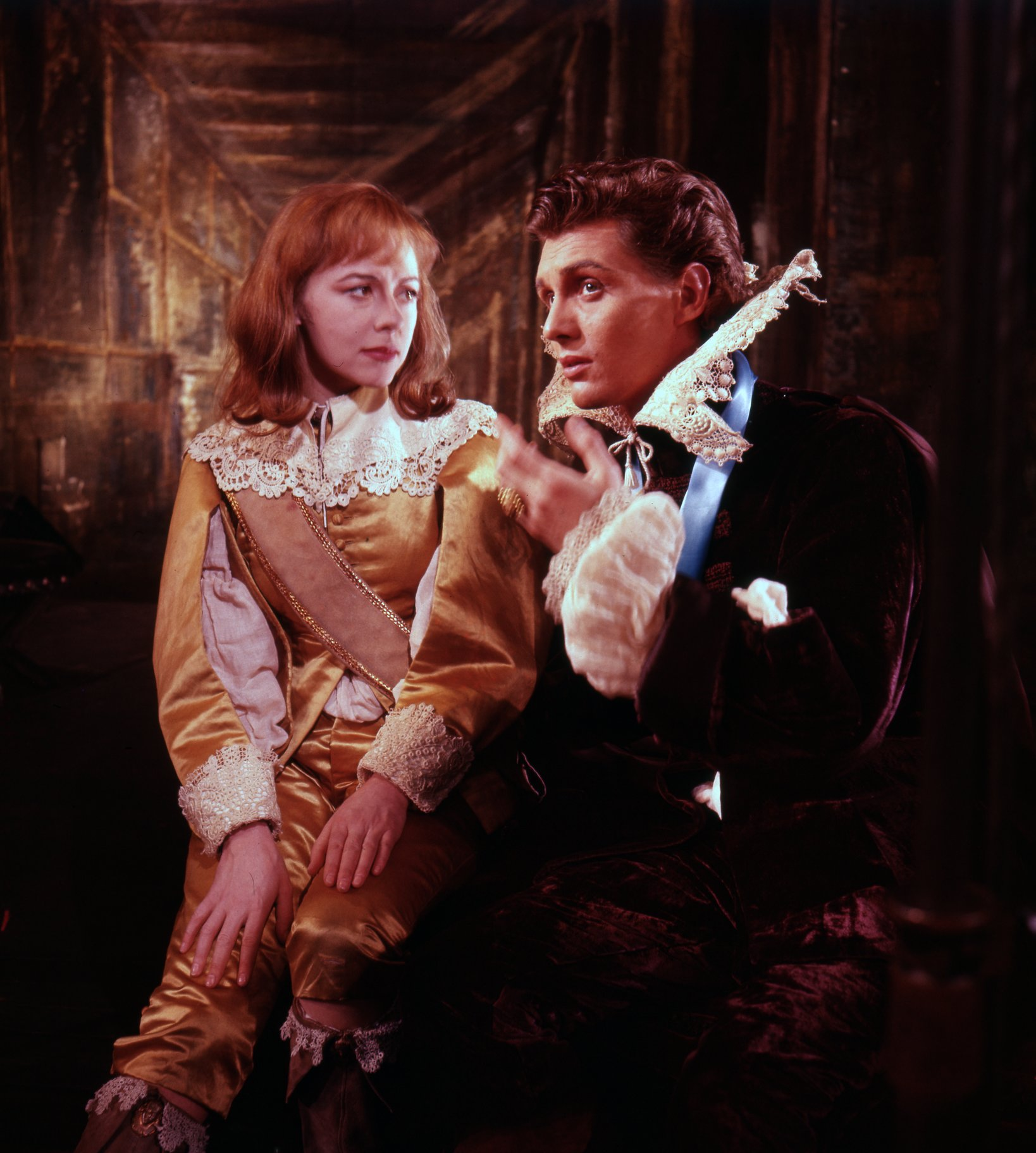 Viola sitting dressed as 'Cesario' in a yellow suit with white ruff and talking to Orsino who looks away into the distance in the 1958 production of Twelfth Night.